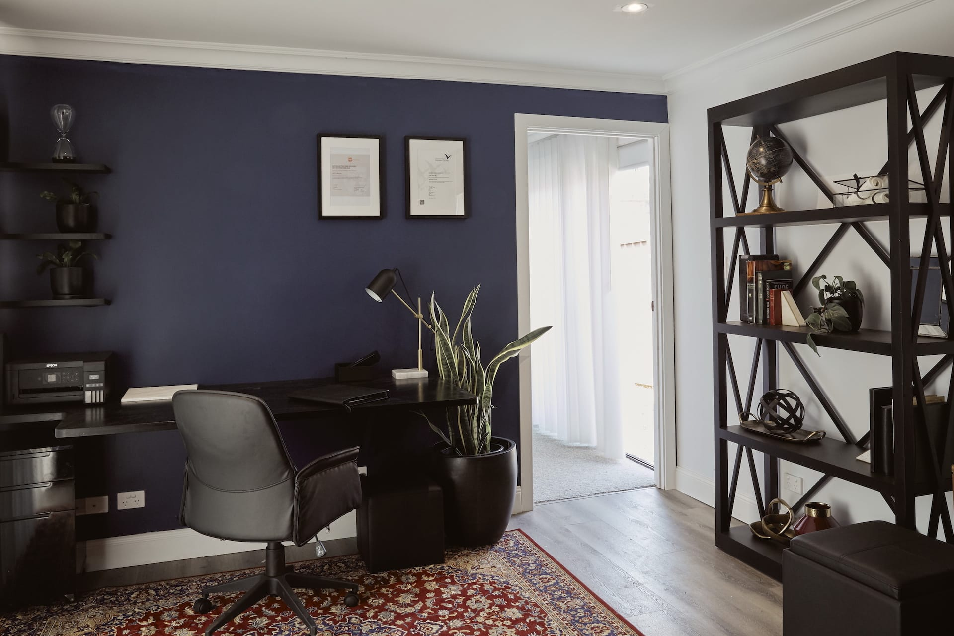 house rules 2020 laith and george home office with black furniture and dark blue feature wall