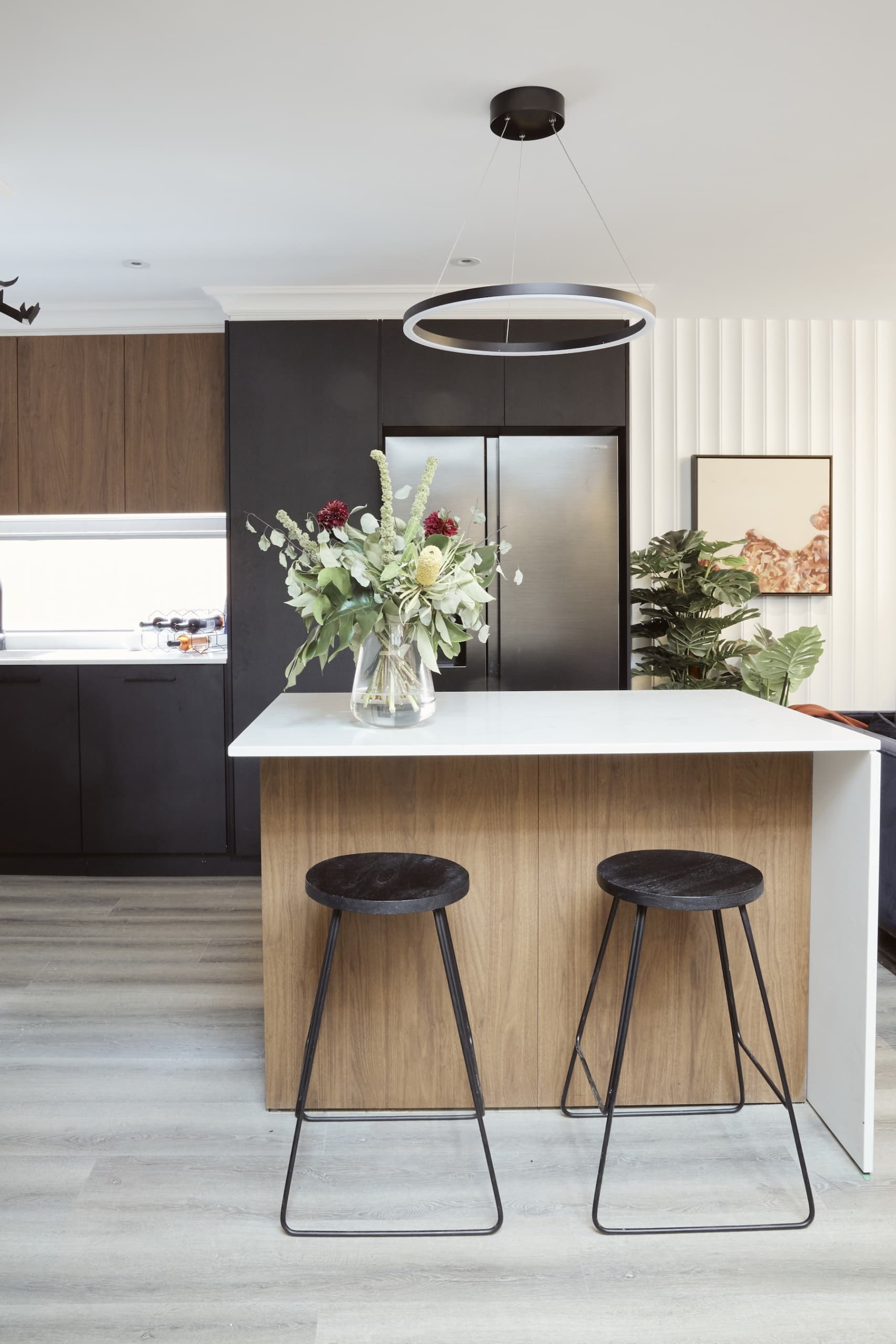 house rules 2020 laith and george kitchen with dark cabinetry and white benchtop