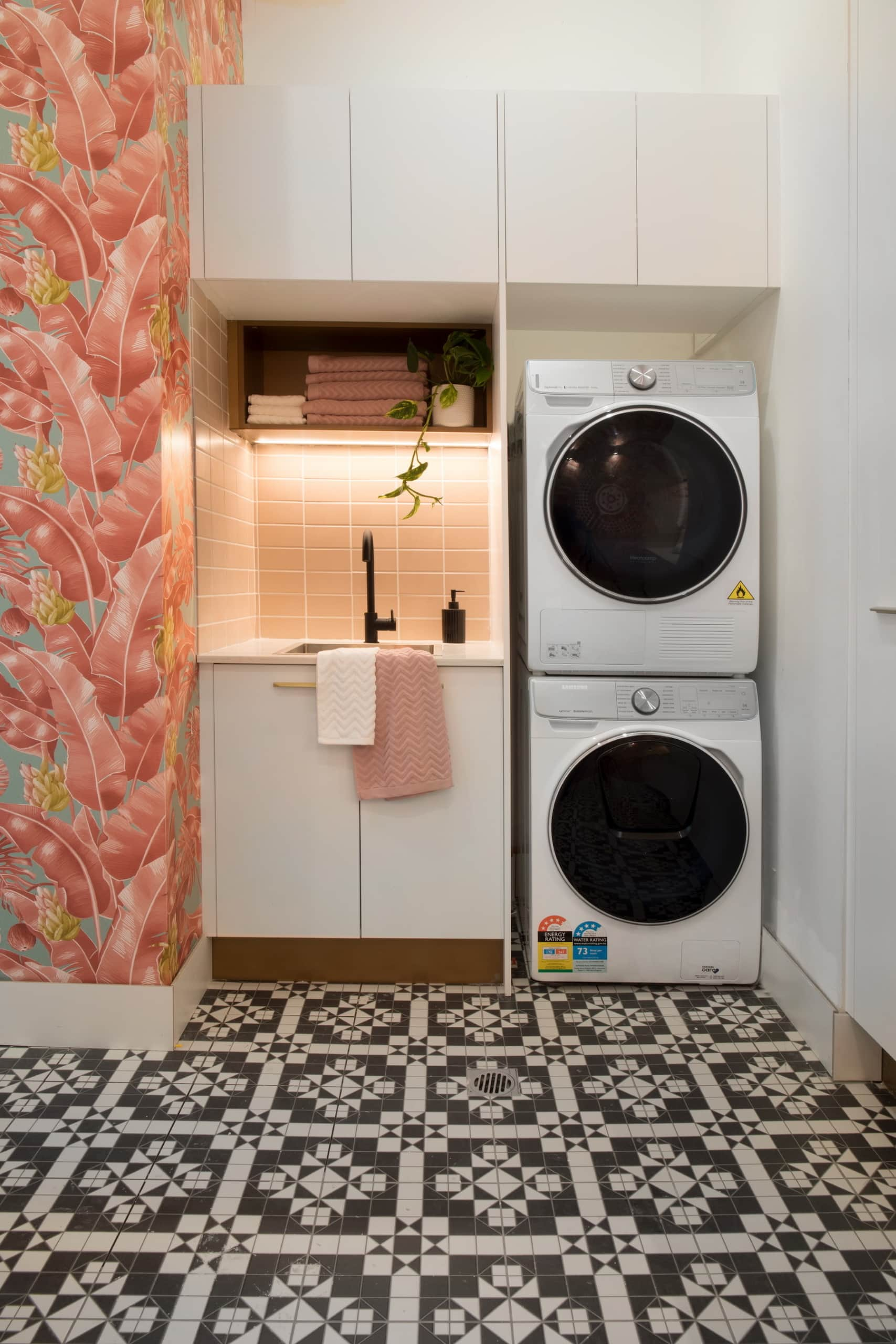 house rules 2020 penthouse reveal laundry with pink wallpaper and black and white floor tiles