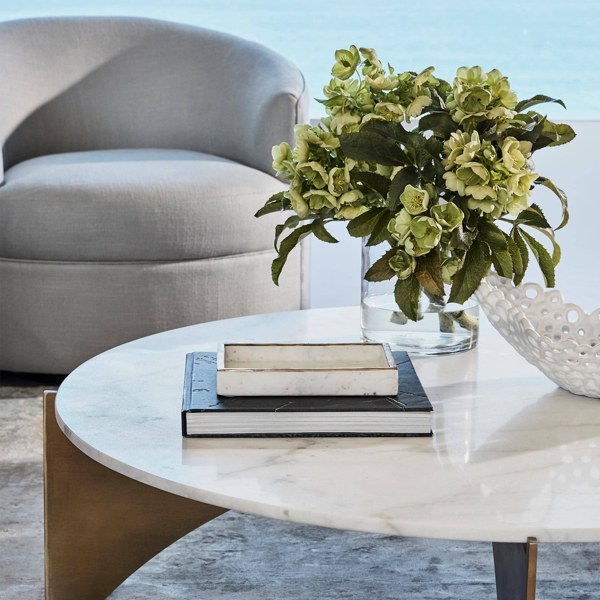 round marble coffee table with minimal coffee table styling flowers and books