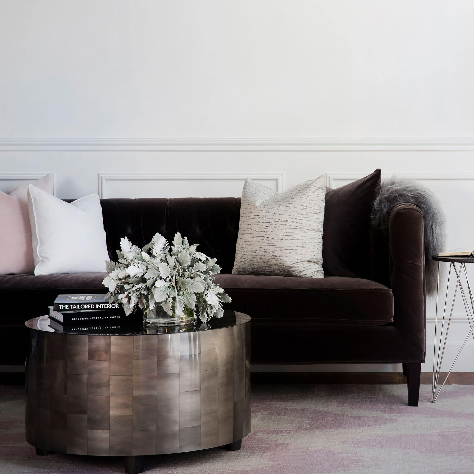 round metallic coffee table coco republic with flowers and stack of books on top