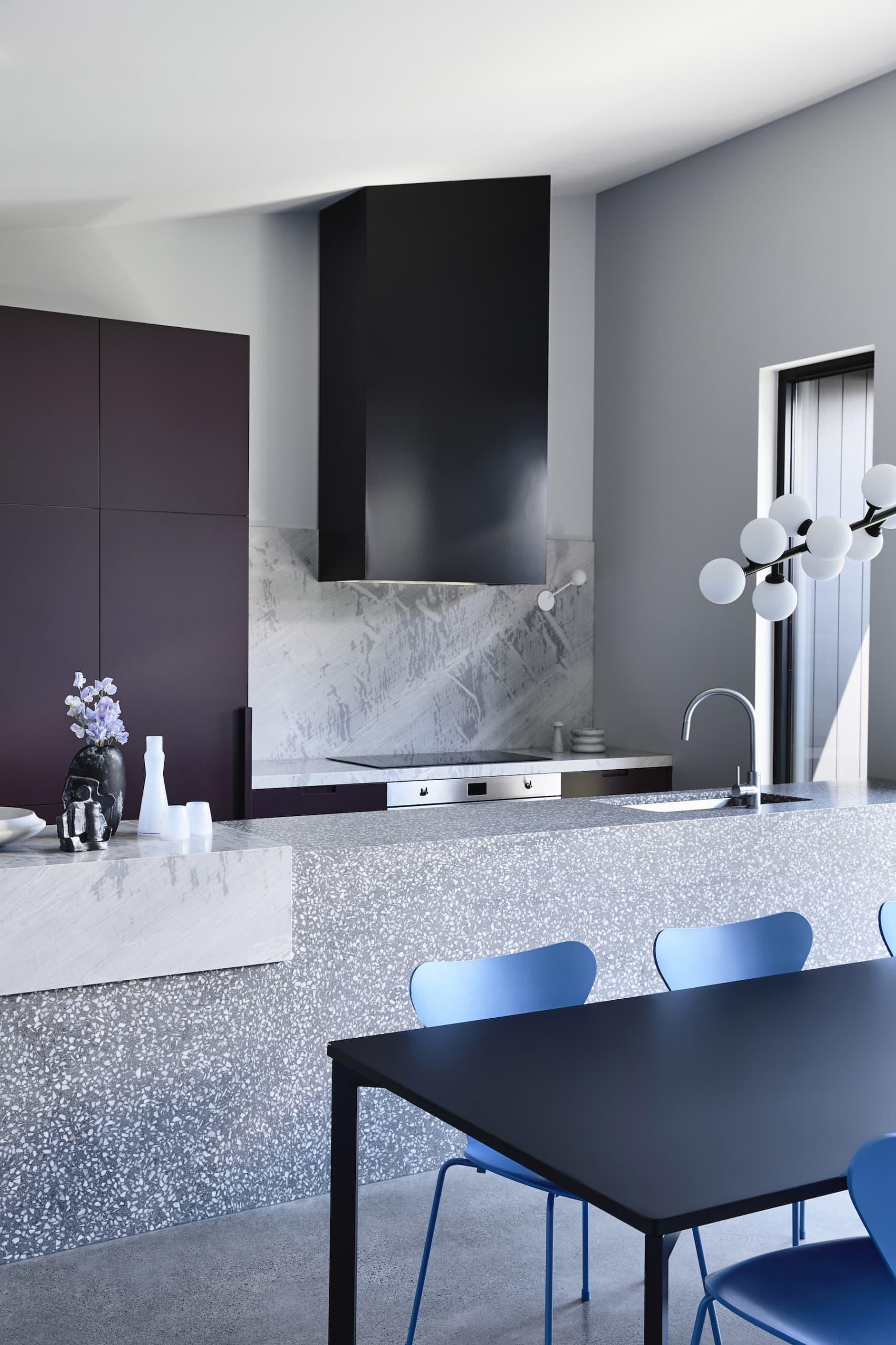 white terrazzo kitchen with black rangehood and purple cabinets