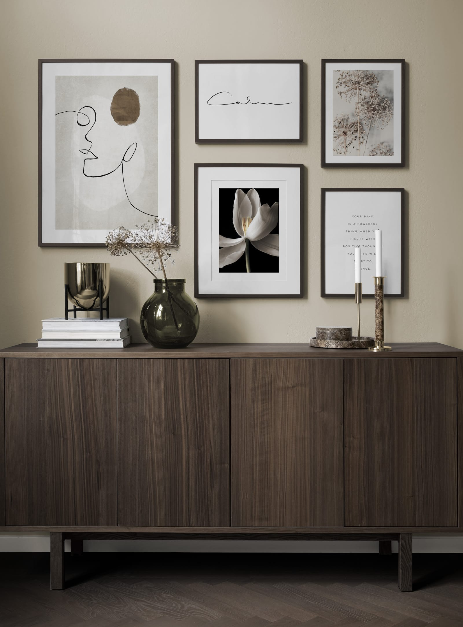 dark timber sideboard with dark timber frame gallery wall above it desenio