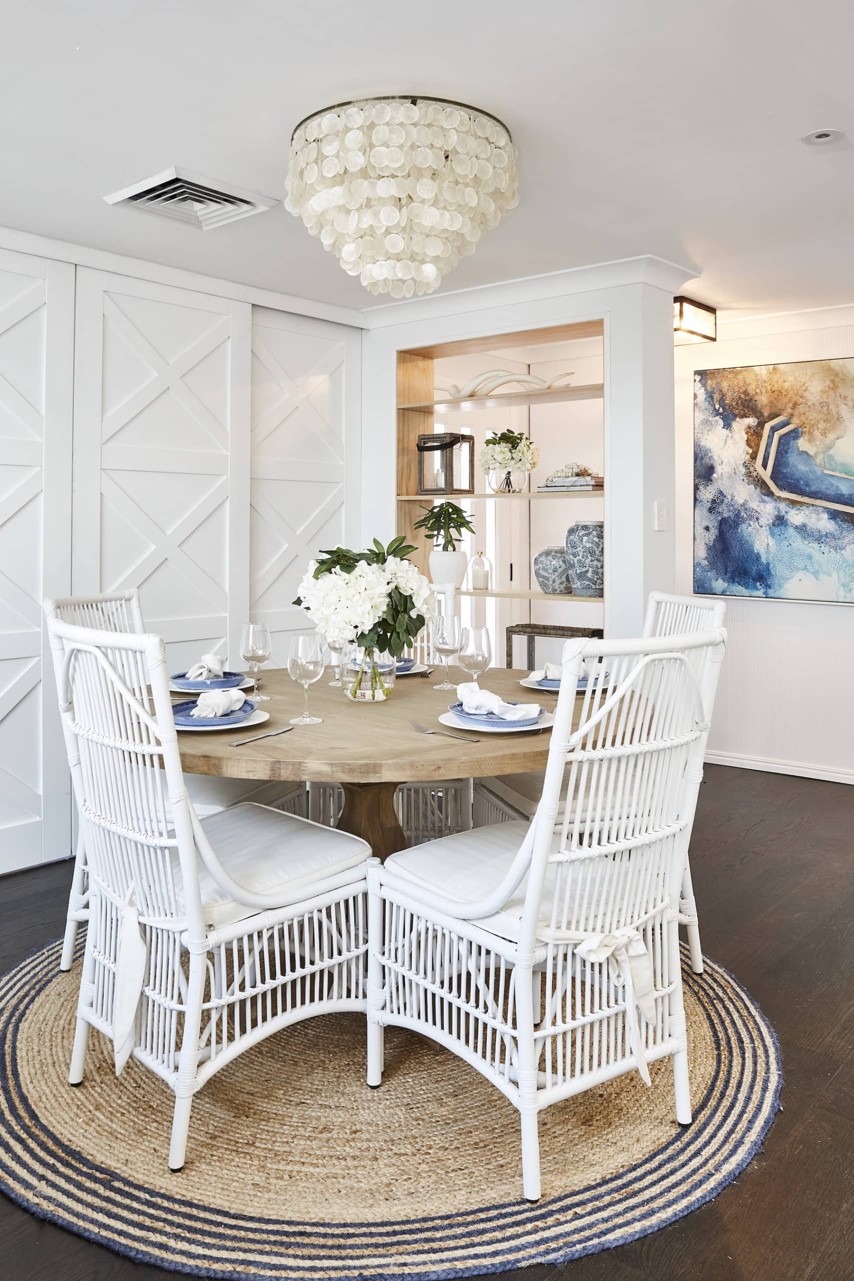 house rules 2020 lenore hamptons dining room with round table and rattan white chairs