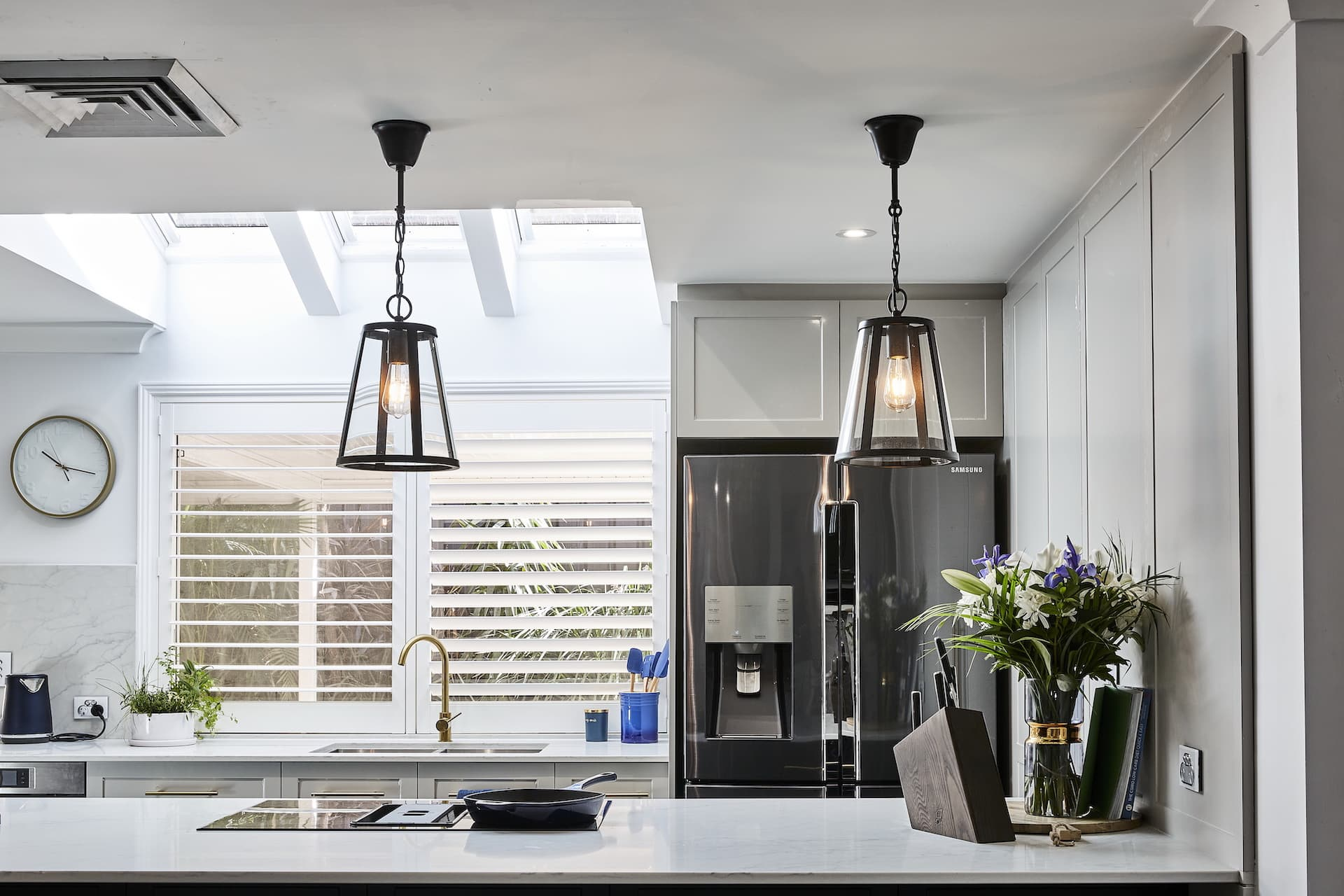 house rules 2020 lenore hamptons kitchen with island and naby blue cabinetry