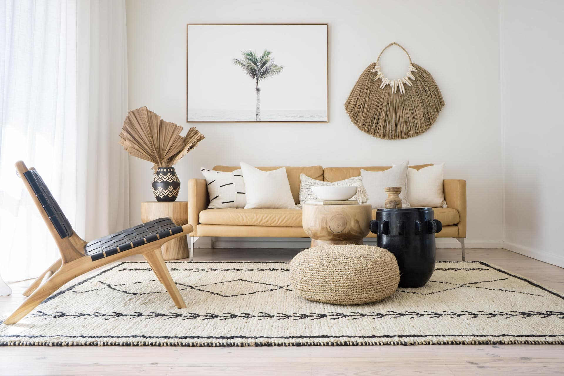 neutral living room with light tan leather sofa boho style round black coffee table