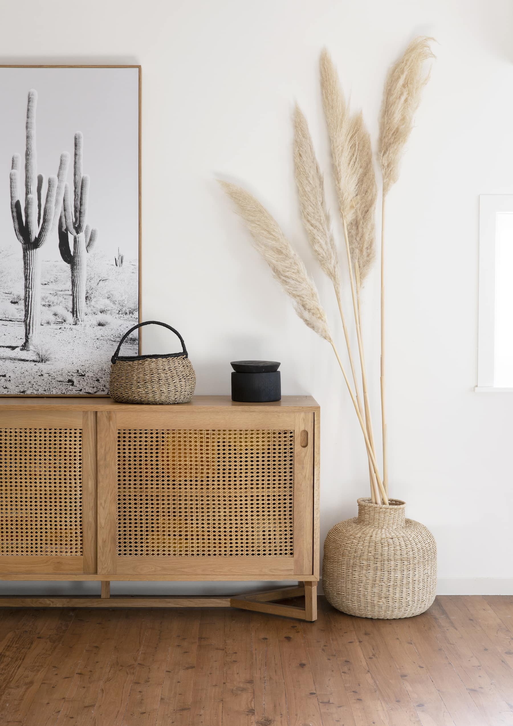 rattan sideboard in bohemian style room with boho art neutral interior design