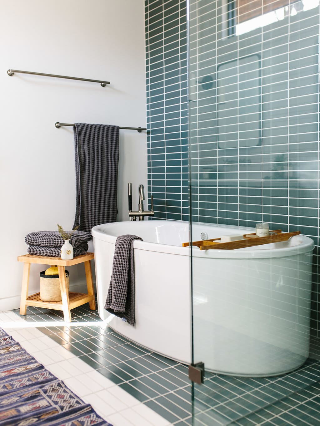 the effortless chic bathroom towel styling hung over bath tub with green wall tiles