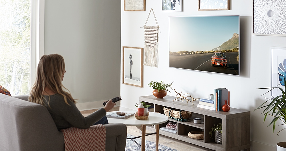 wall mounted tv woman watching tv with remote