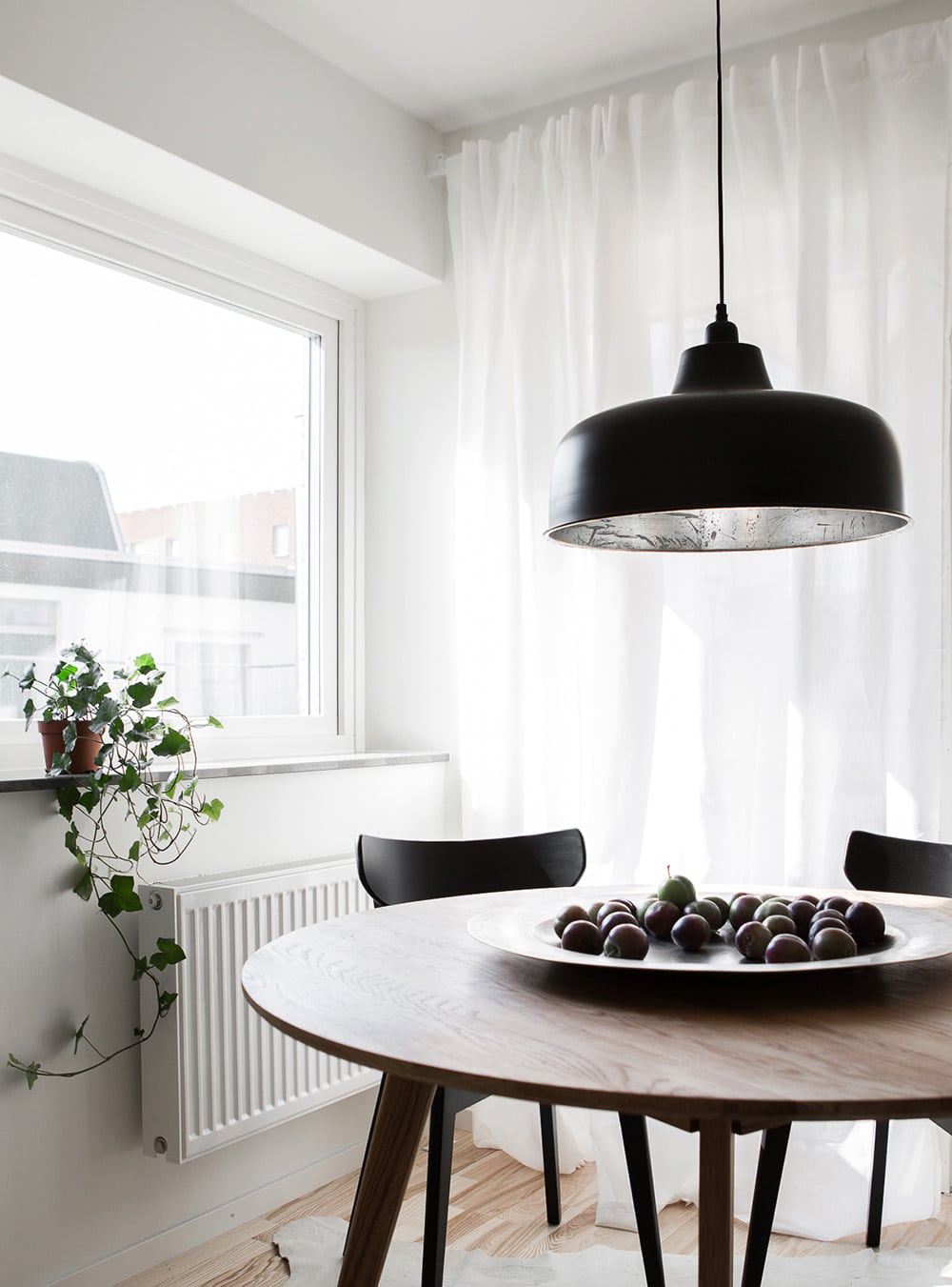 large black round pendant light over small round timber dining table