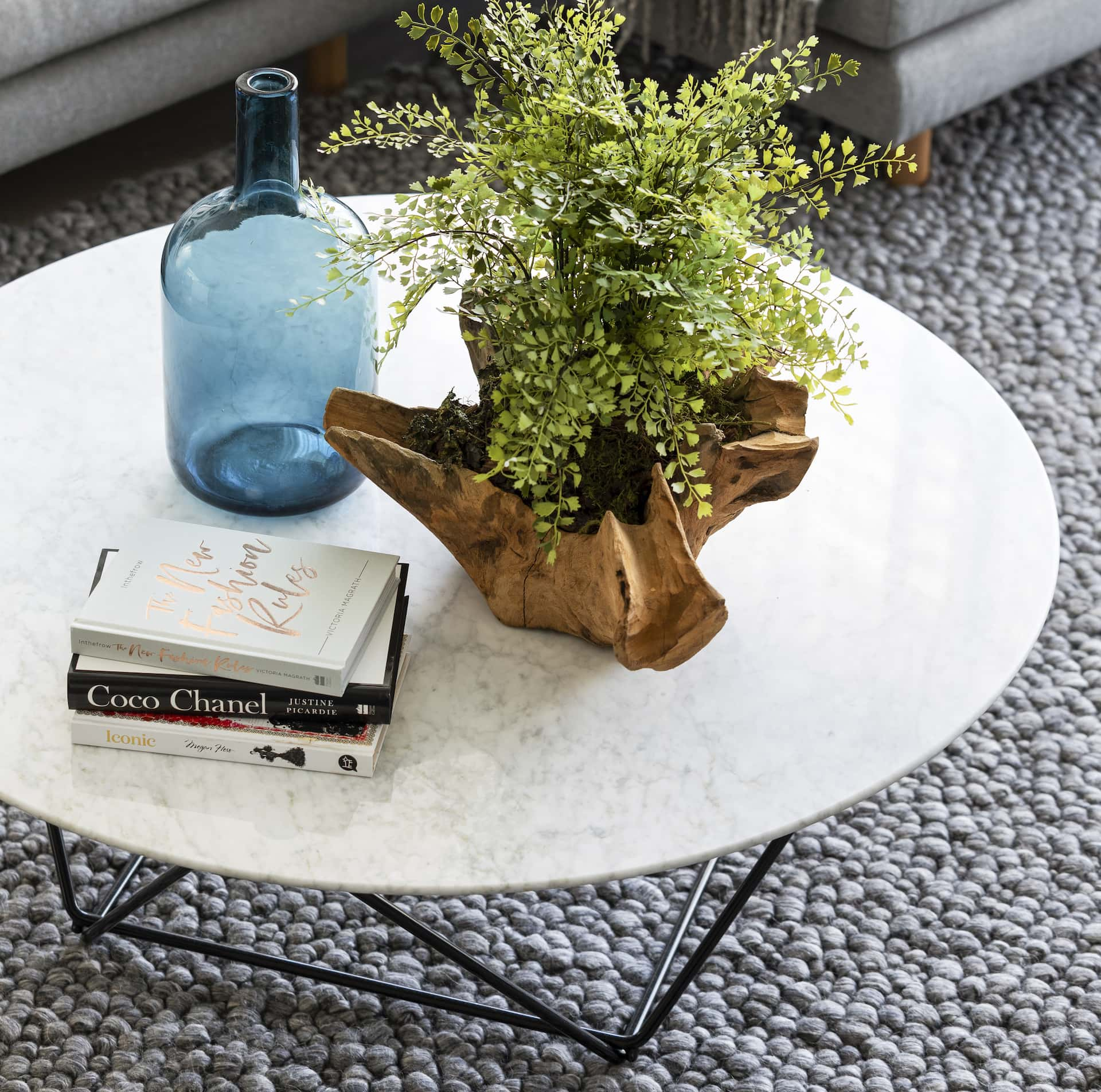 round marble coffee table with black metal legs and book stack
