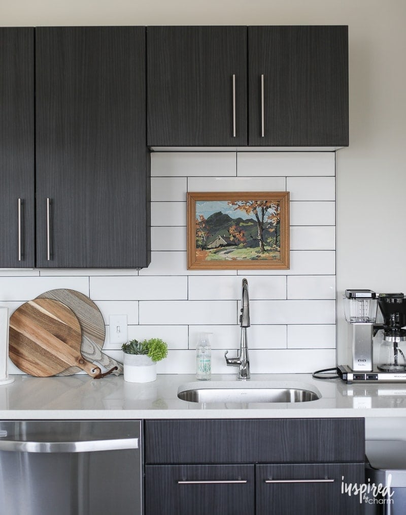 dark kitchen cabinets with white splashback tiles