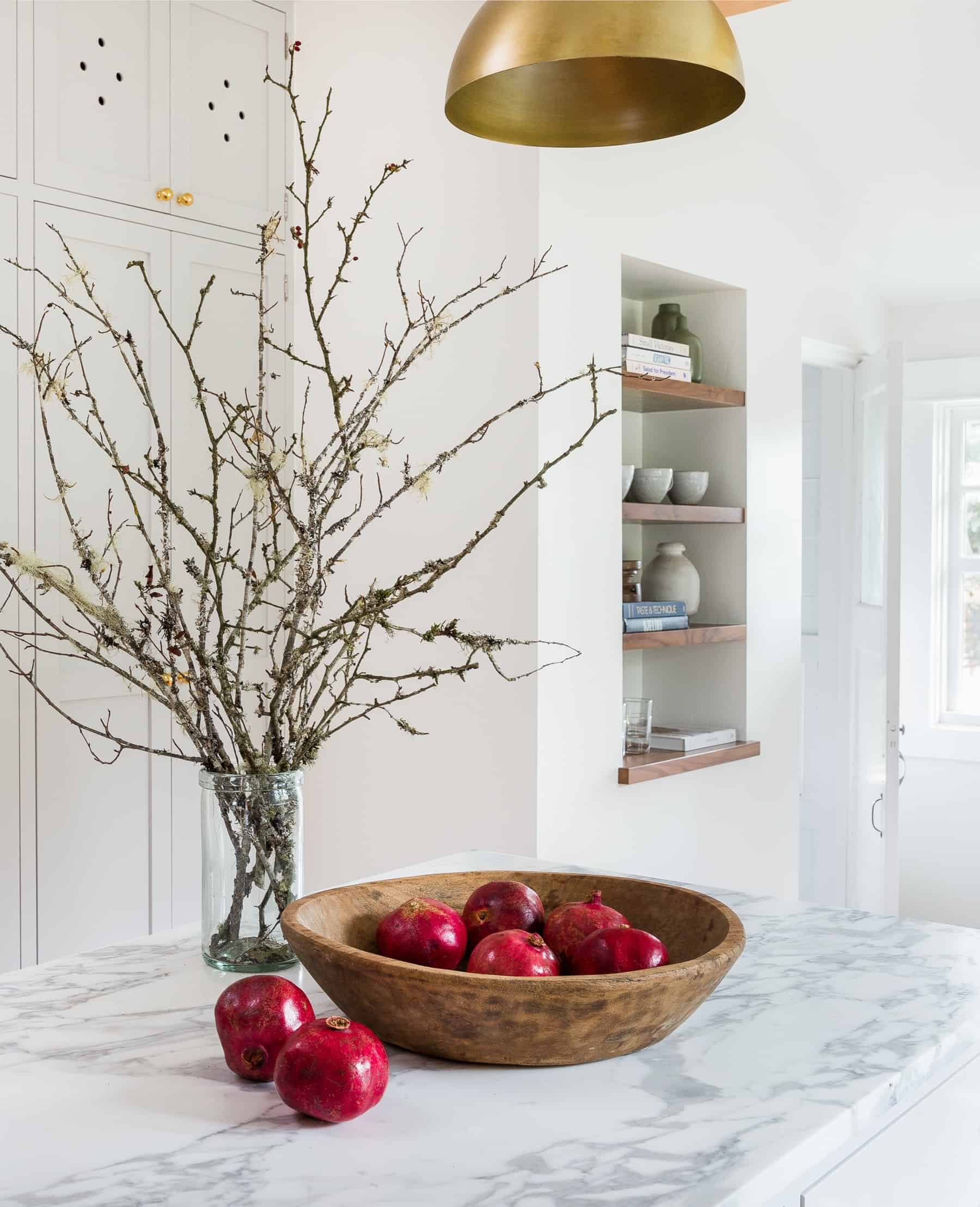 large vase with twigs stems and large round fruit bowl