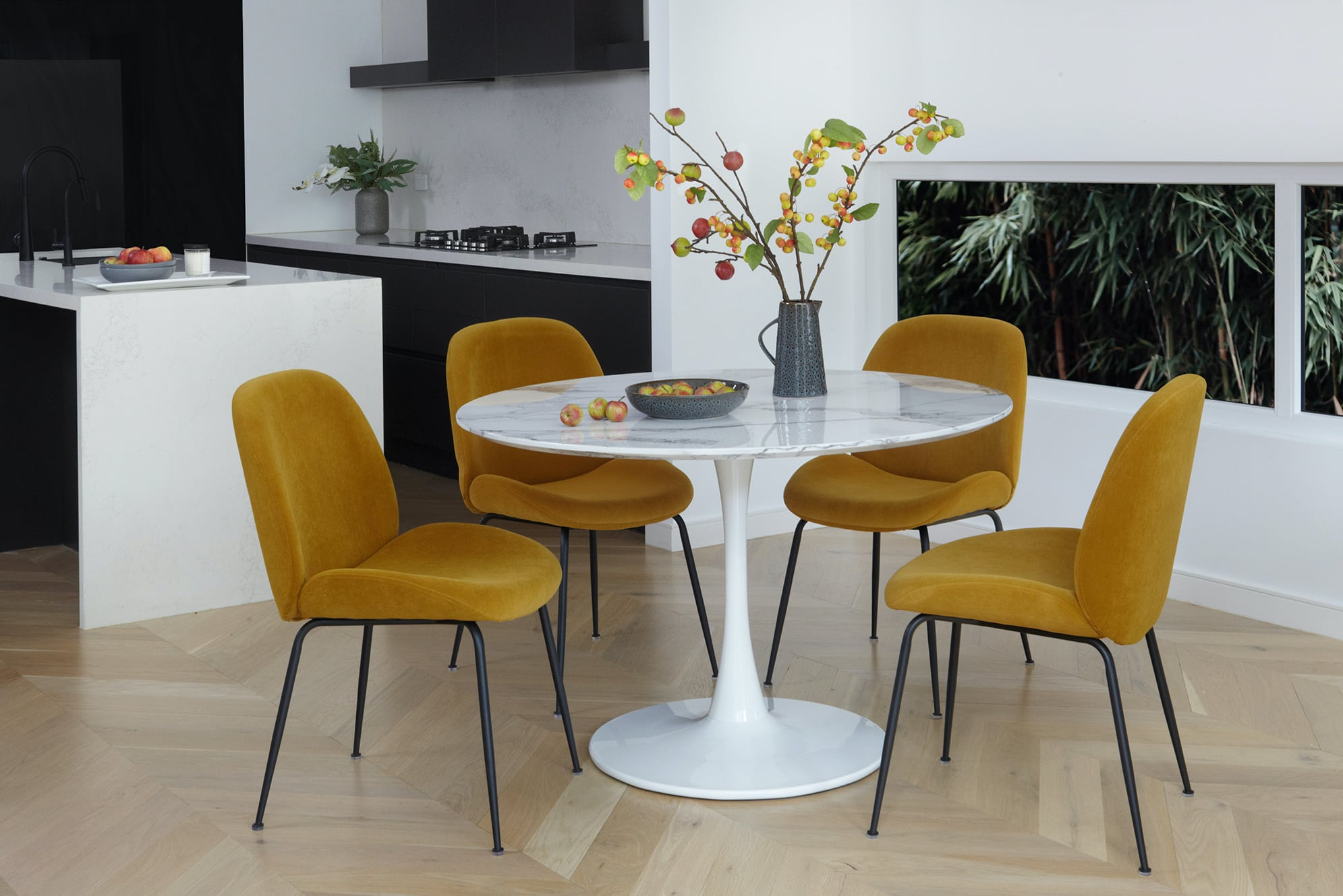 mustard velvet dining chairs with round marble dining table in luxe apartment