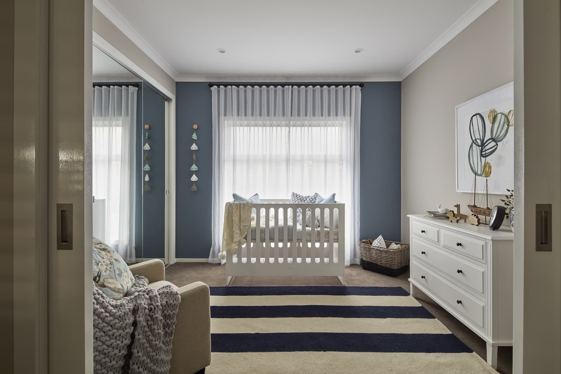 baby nursery with dark blue feature wall white hamptons dresser and blue and white stripe rug