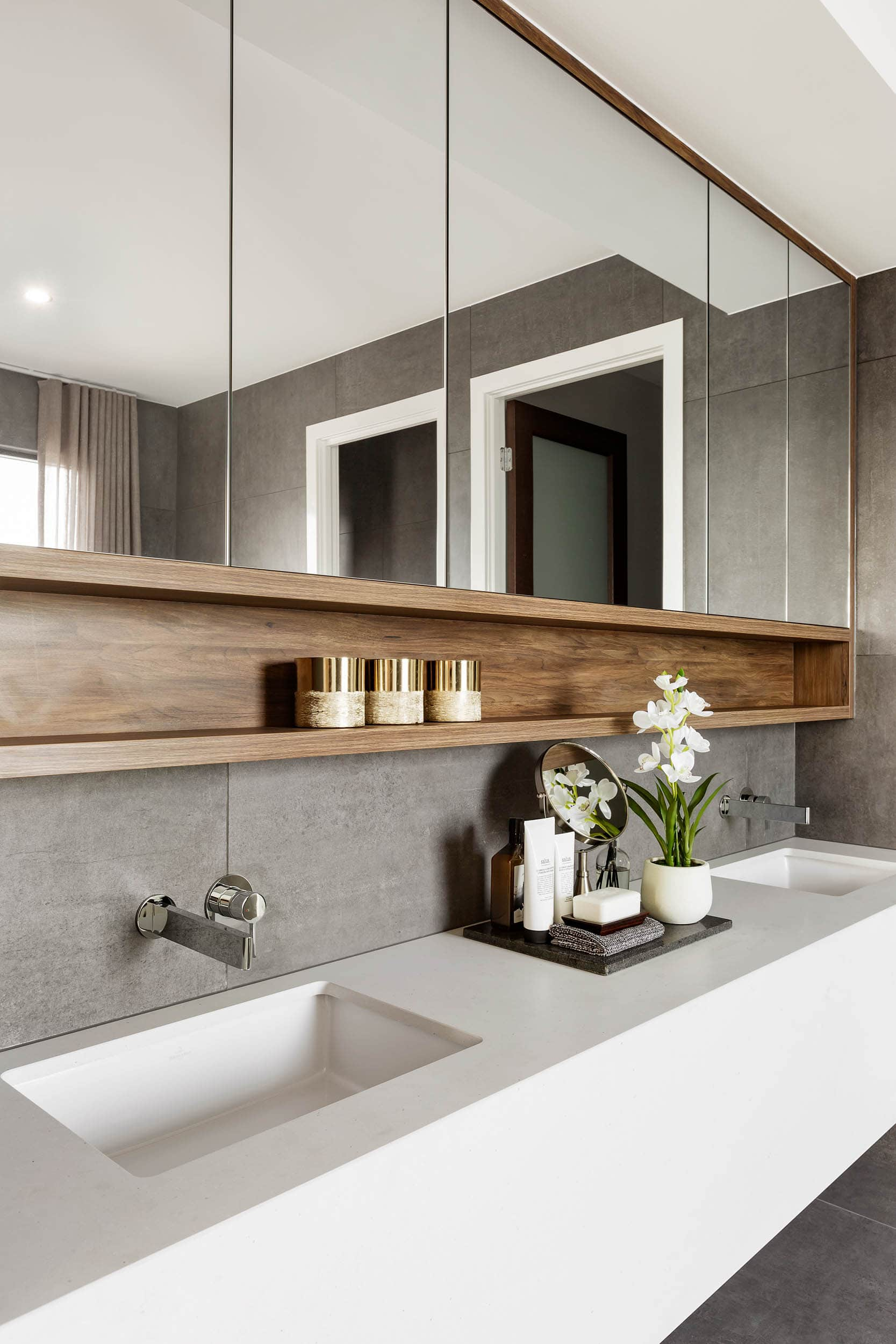 bathroom with matte grey wall tiles white floating stone vanity and shaving cabinet
