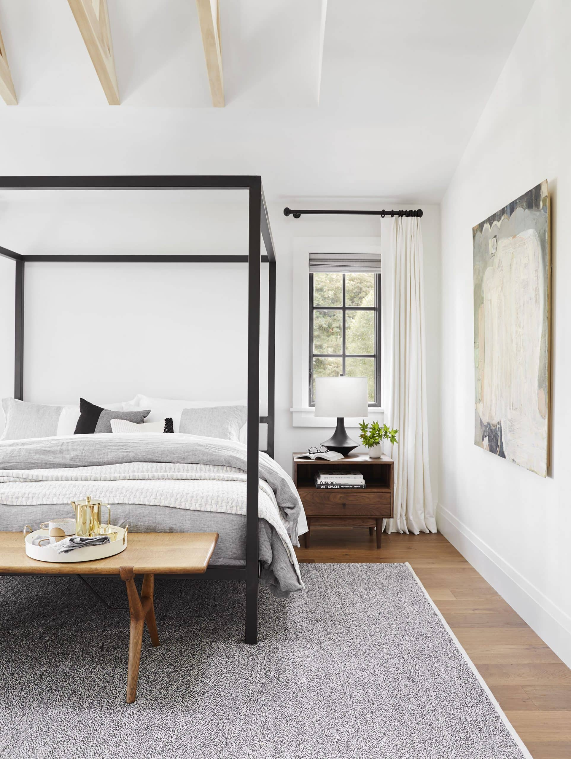 bedroom with black four poster bed and mid century nightstand california cool