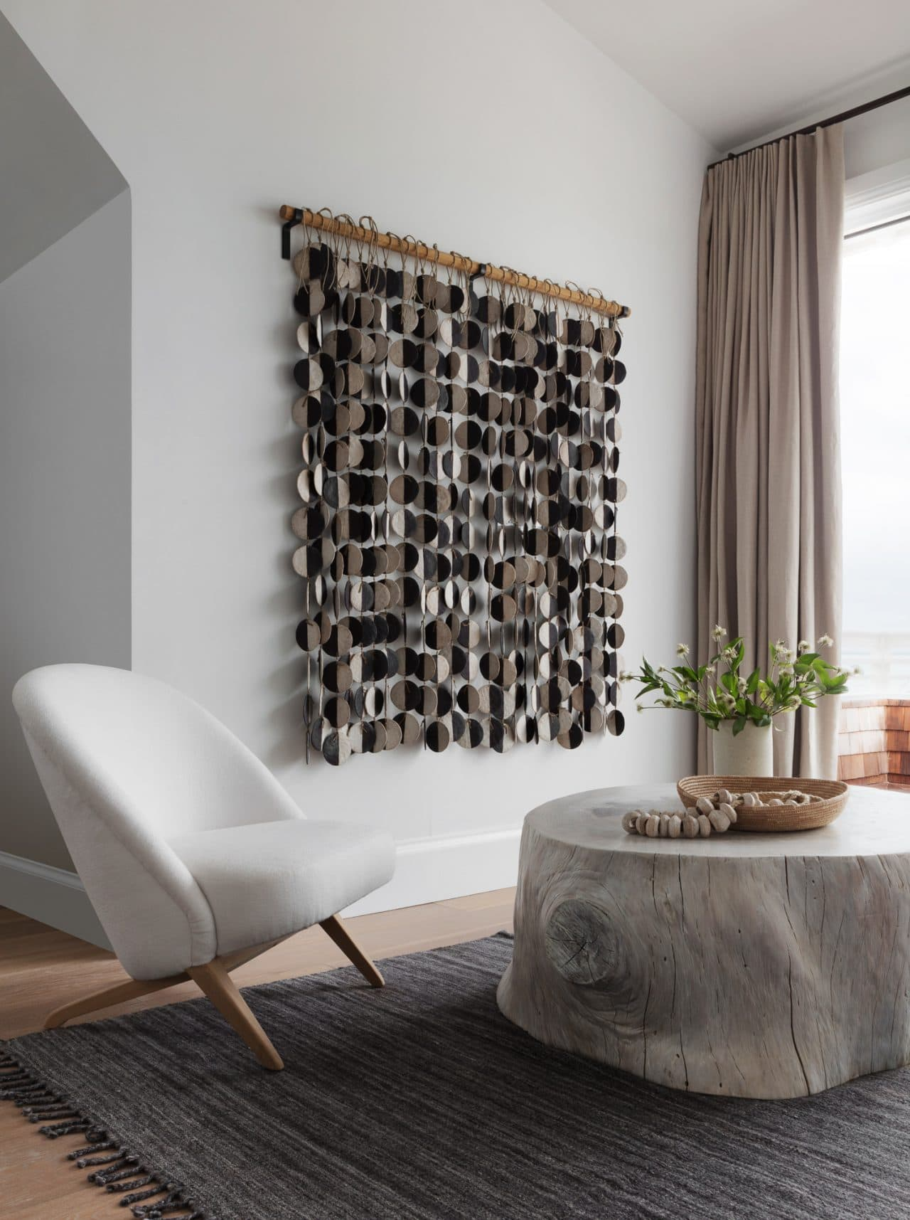 bobby berk bedroom with large handmade art tapestry on wall above reading nook