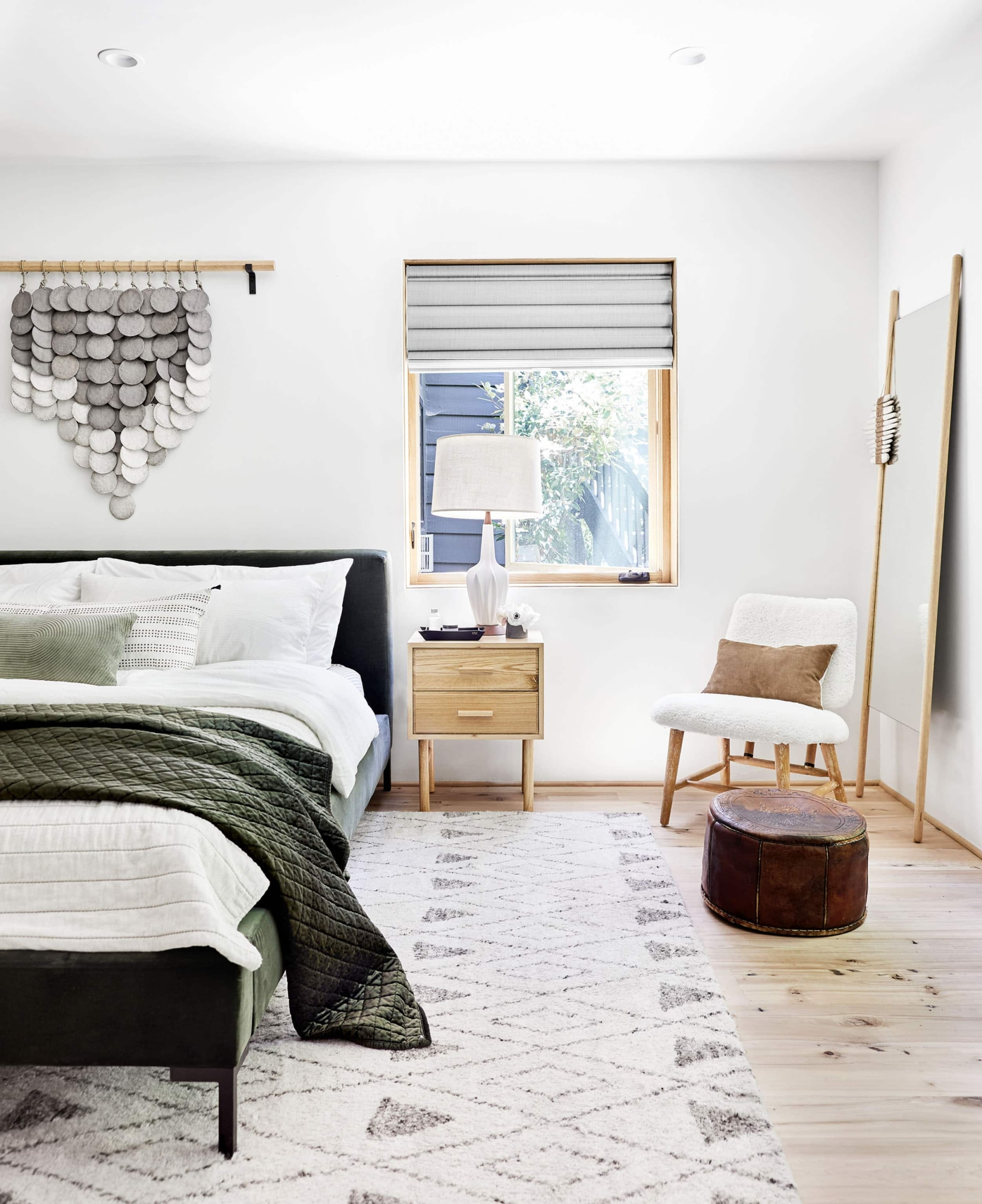 california cool bedroom with scandi bedside table mid century table lamp and textile hung above bed