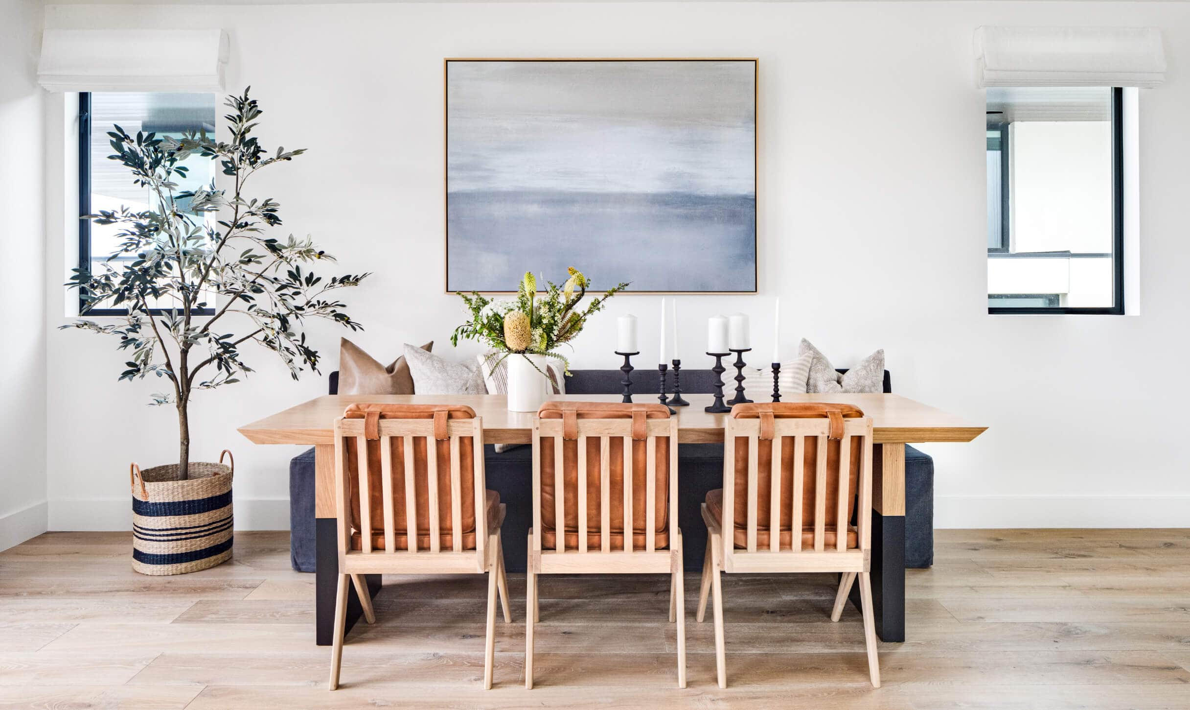 california cool dining room with woven leather dining chairs and large olive tree in rattan basket