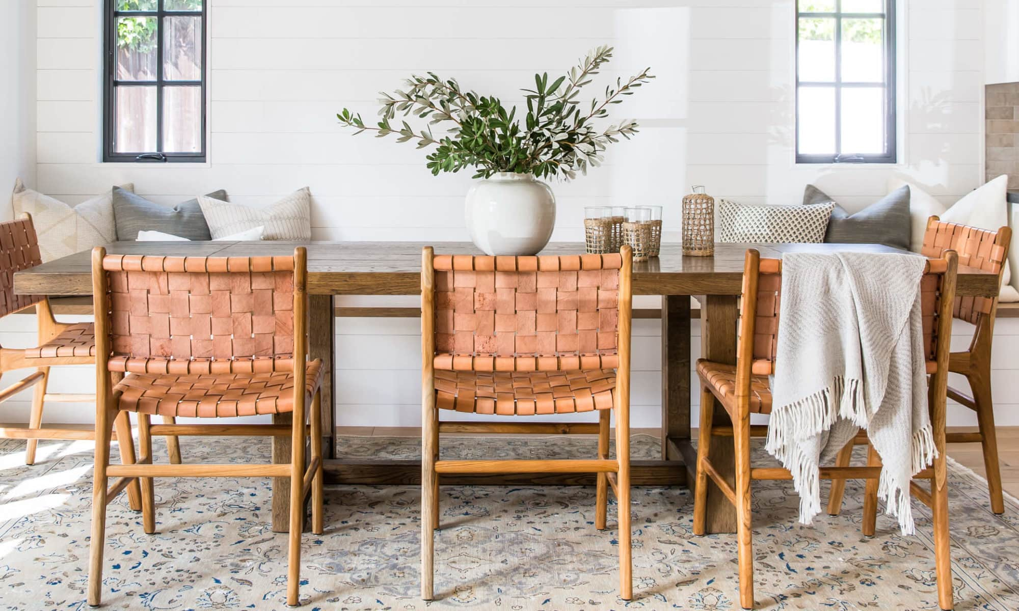 california cool interior design dining room with woven leather dining chairs and rustic table