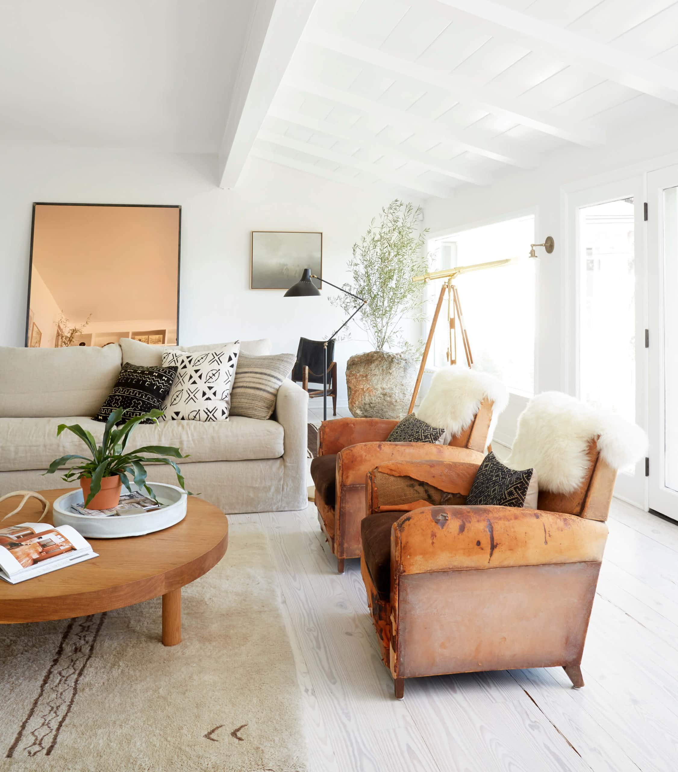 california cool living room with vintage leather armchairs and mid century lighting