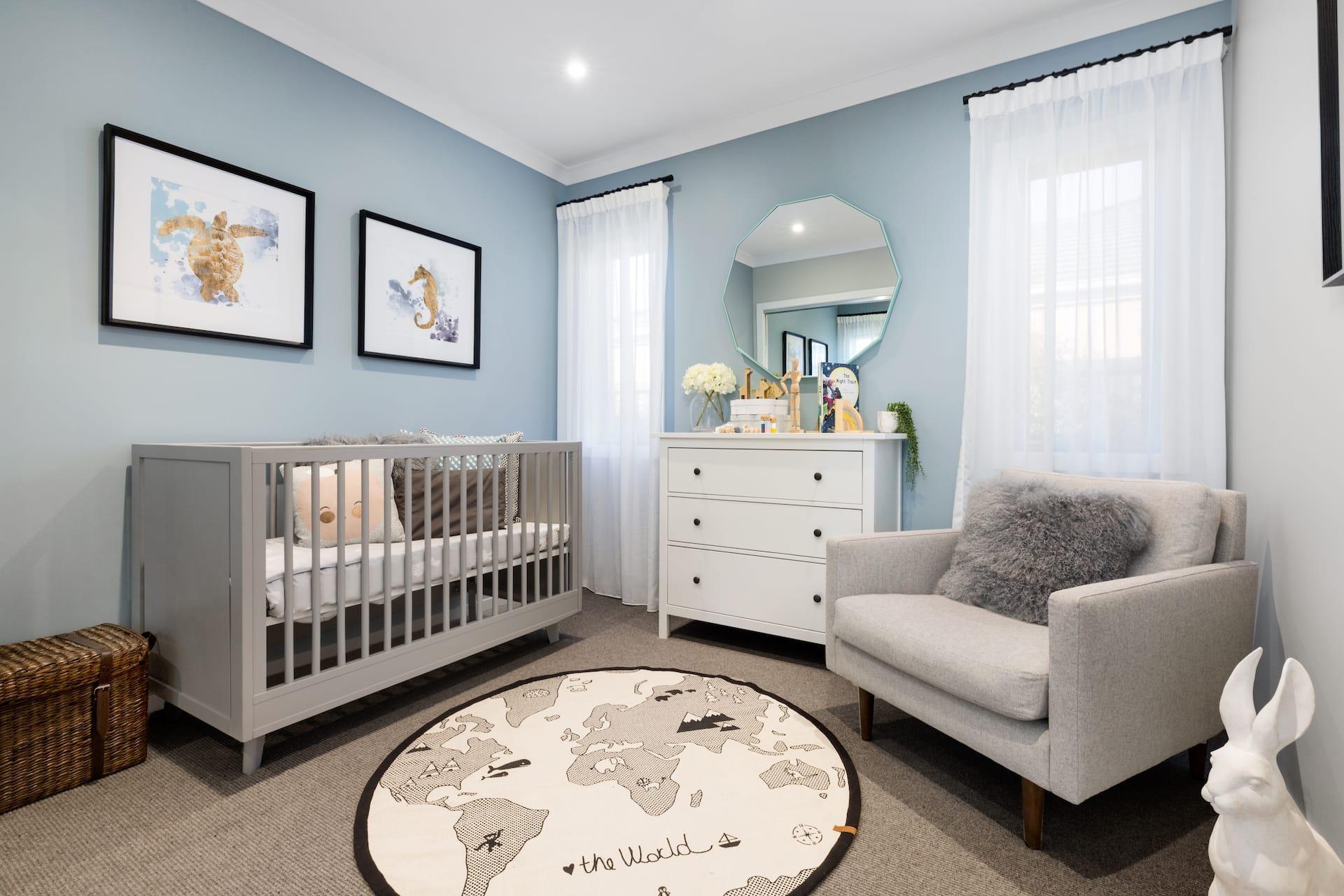 gender neutral nursery design with light blue walls grey crib and sea animal artworks
