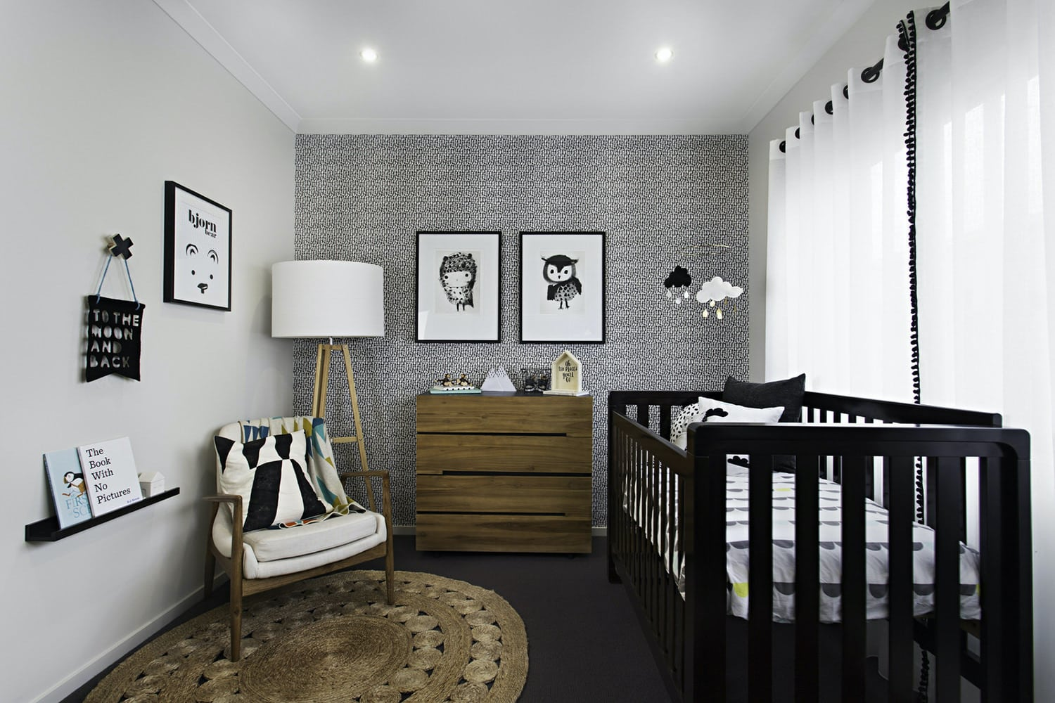 gender neutral nursery with black and white wallpaper black crib and round jute rug