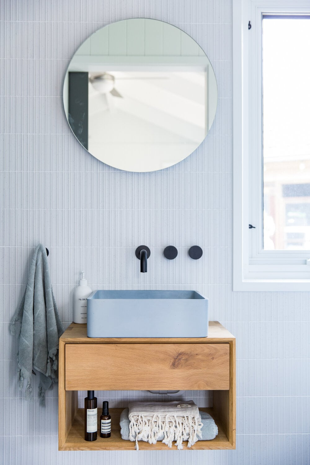 light blue coloured basin in bathroom with floating timber vanity and black taps