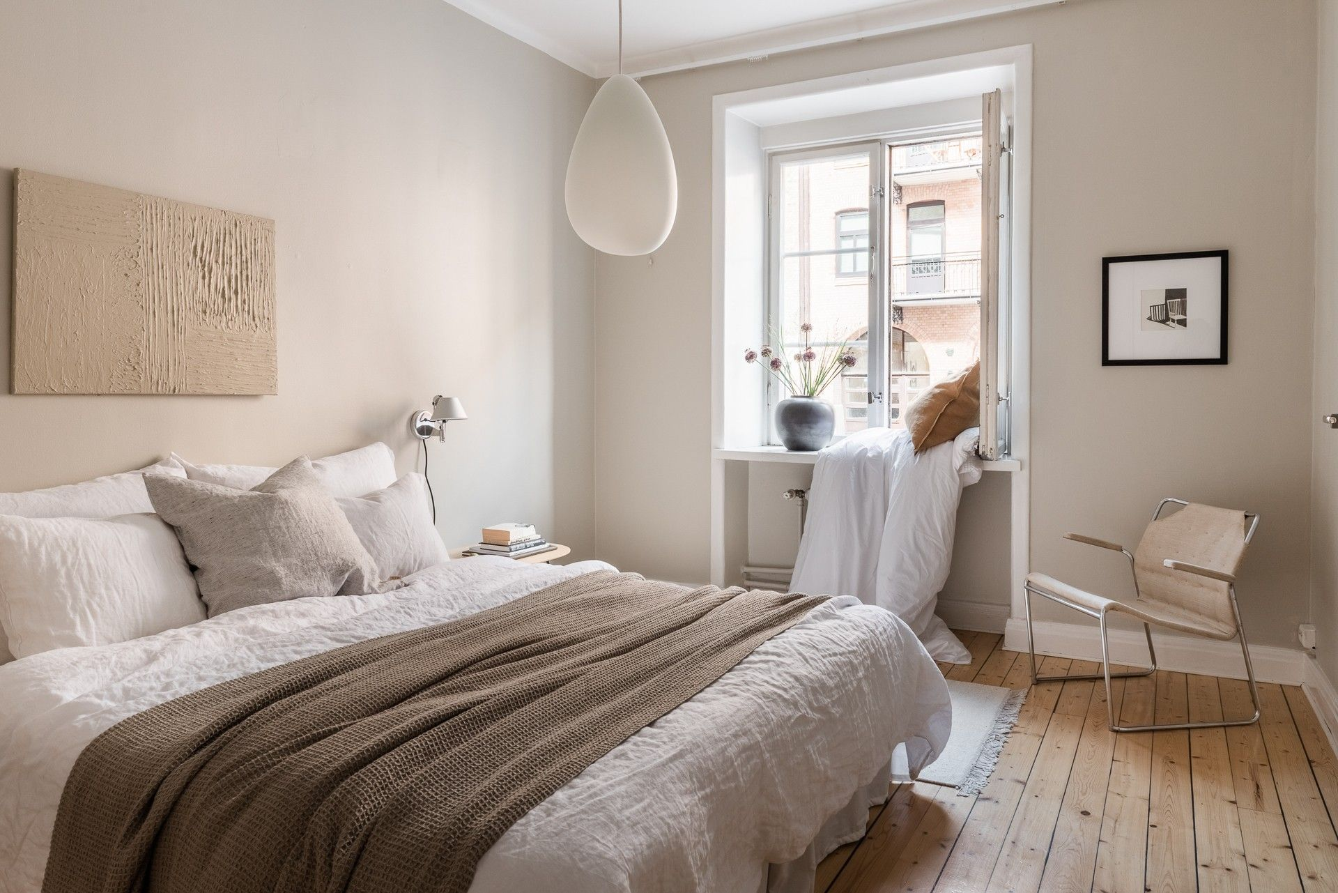 light pink scandinavian bedroom design with light floorboards and white bedding