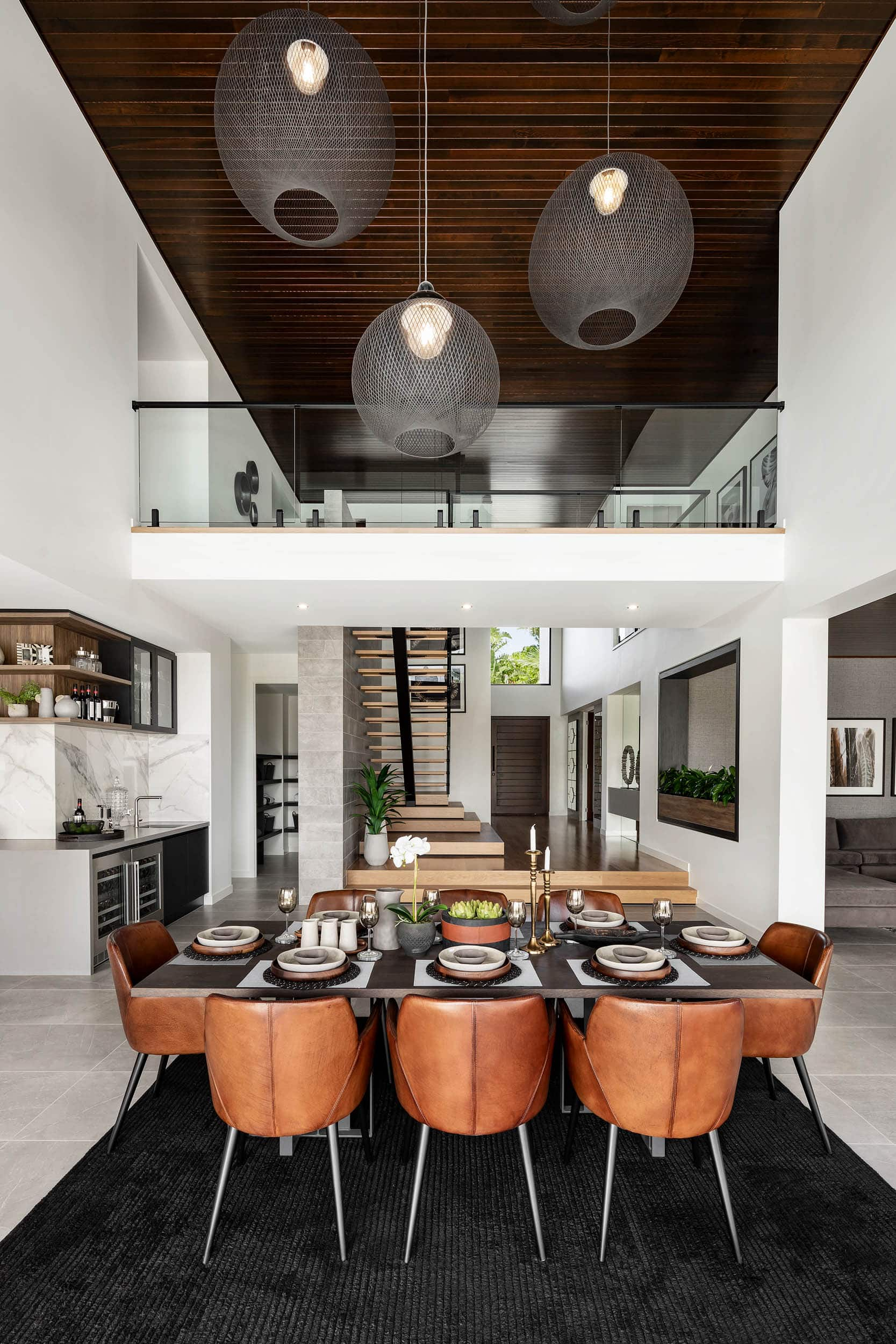 modern dining room with black table and tan leather dining chairs