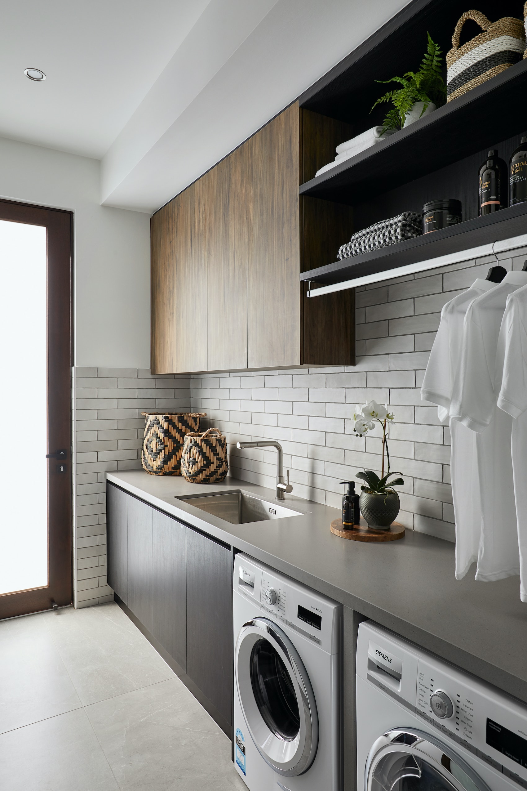 modern laundry with white subway tiles and brown cabinets grey grout
