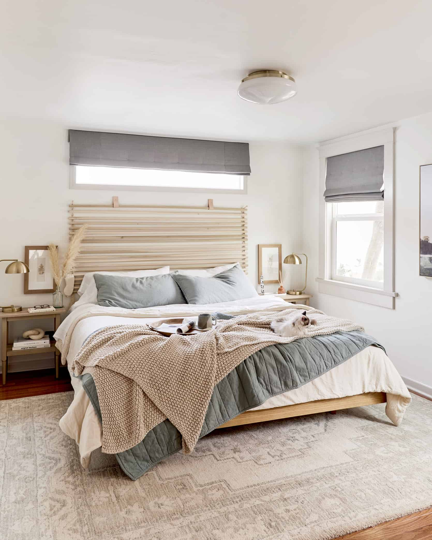 neutral bedroom design with light blush and blue bedding and oak timber bed