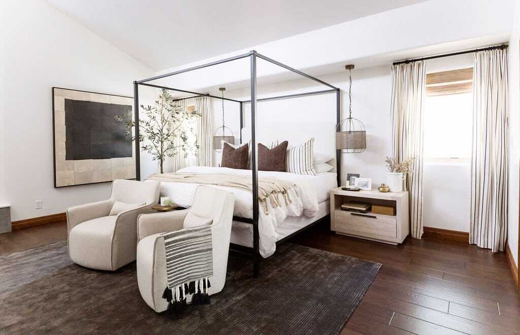neutral master bedroom with black four poster bed and beige armchairs with dark rug