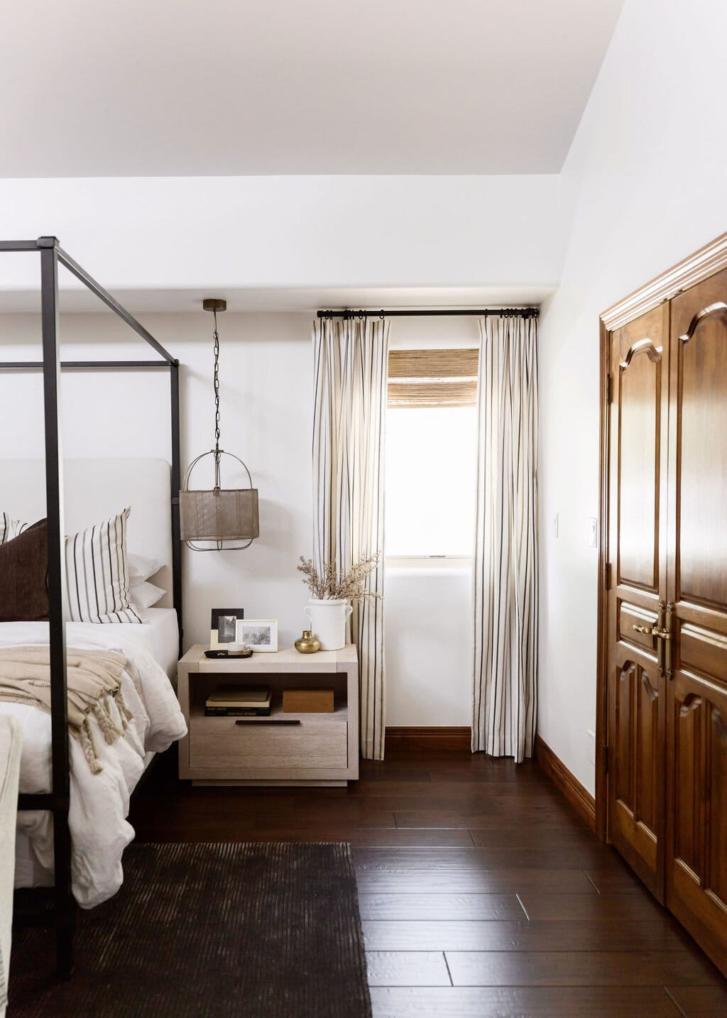 neutral master bedroom with dark brown floorboards and black four poster bed