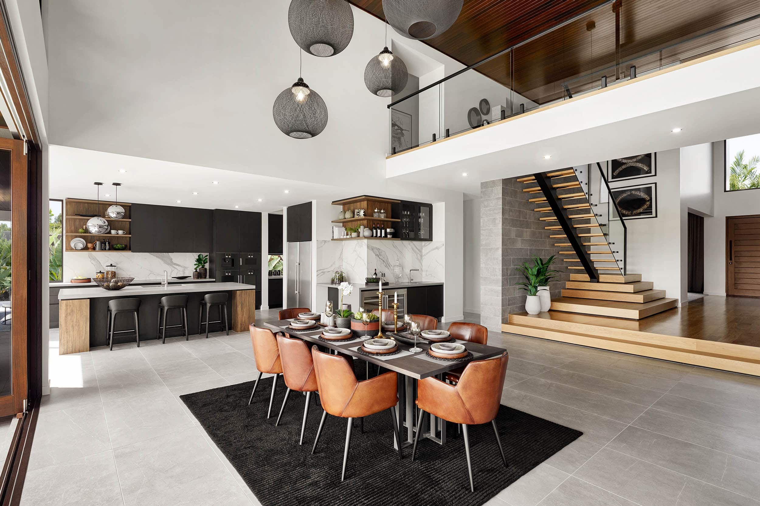 open plan kitchen and dining room with dark grey floor tiles and cluster of black mesh pendants over table