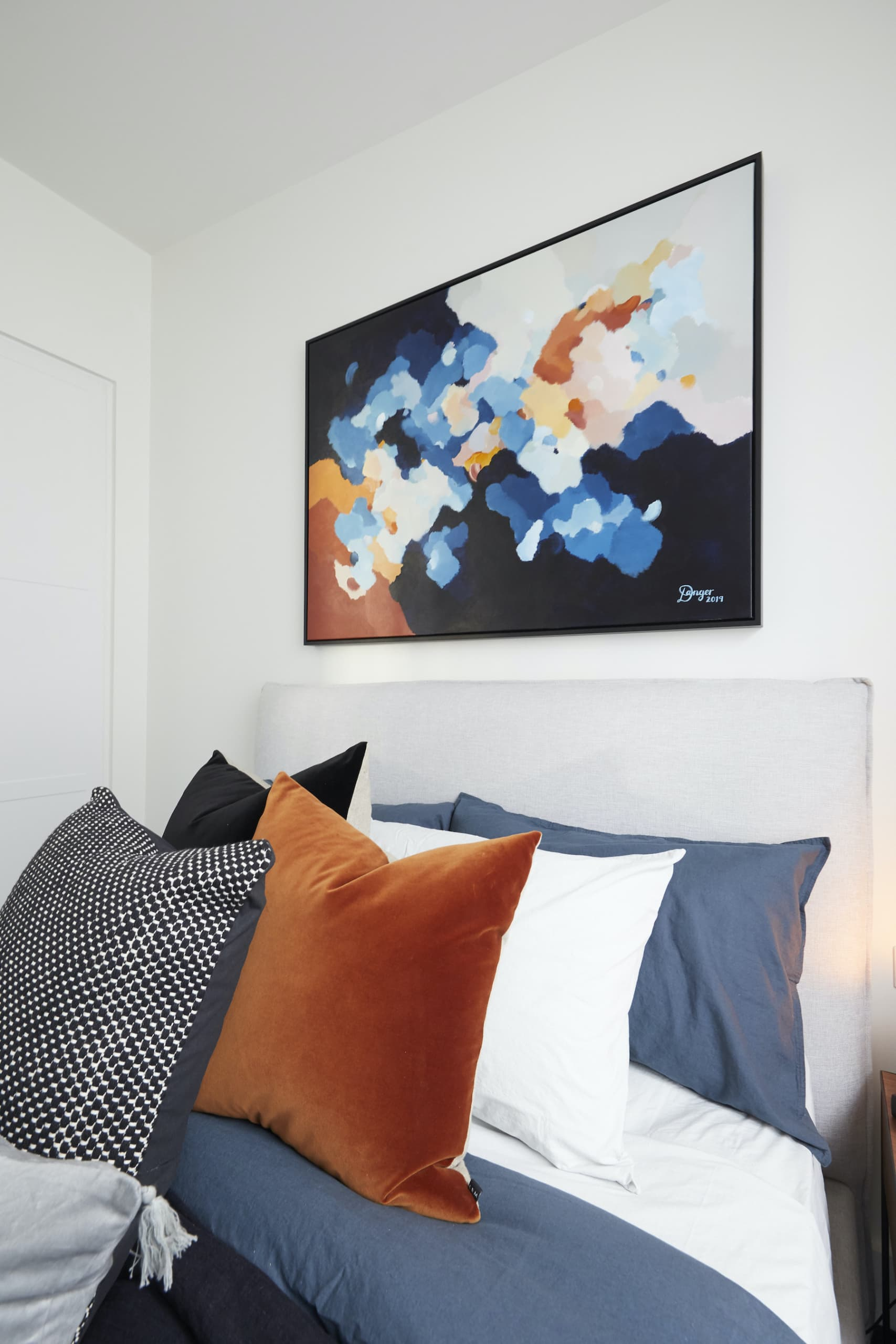 the block 2020 harry and tash upstairs bedroom with blue and orange bedding and abstract art