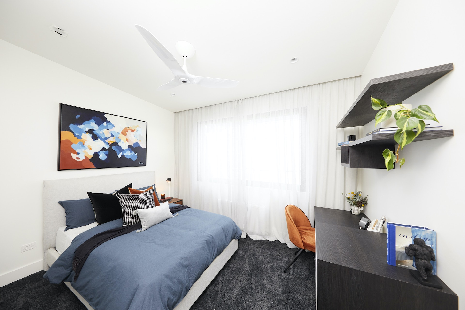 the block 2020 harry and tash upstairs bedroom with charcoal carpet blue bedding and orange accents