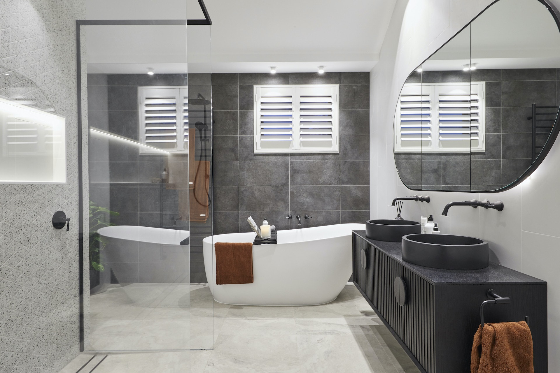 the block 2020 sarah and george upstairs bathroom with dark grey matte wall tiles and freestanding bath
