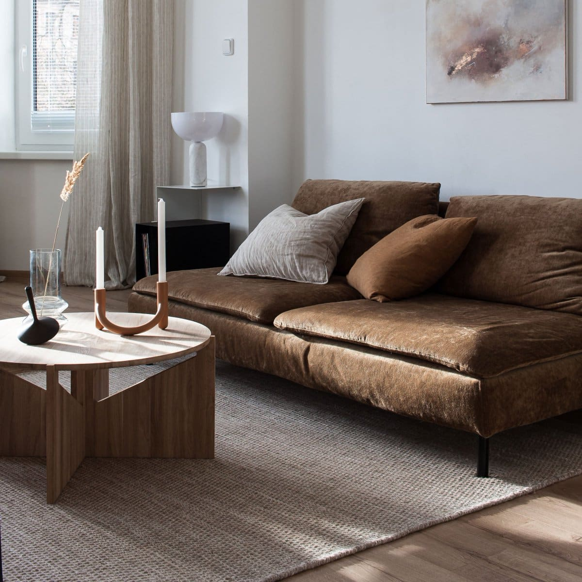 brown sofa in neutral living room with round marble coffee table