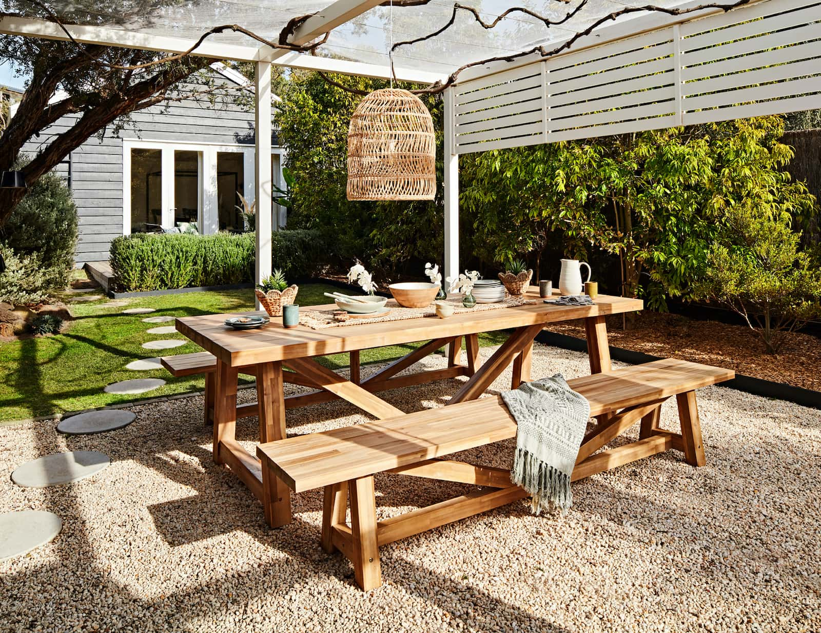 early settler reclaimed teak outdoor furniture dining table and benches in backyard
