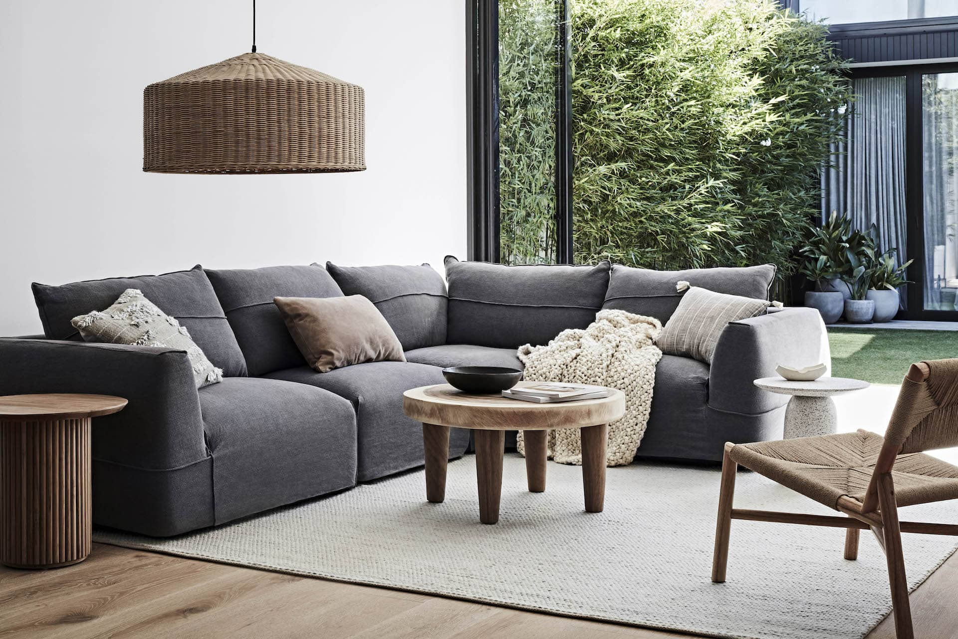 globewest dark charcoal sofa in neutral living room with beige rug and timber tables