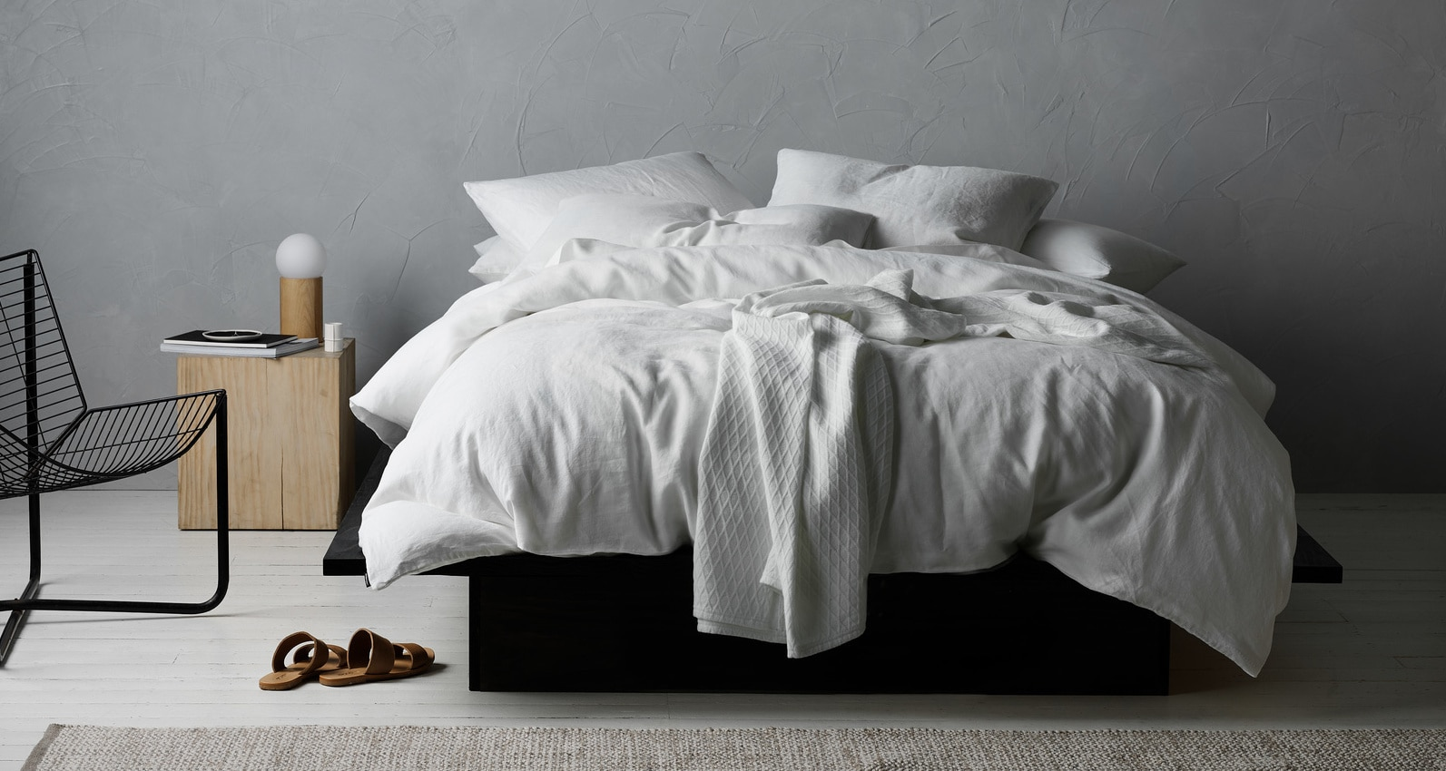 lorraine lea white quilt cover set on bed in grey bedroom with concrete feature wall