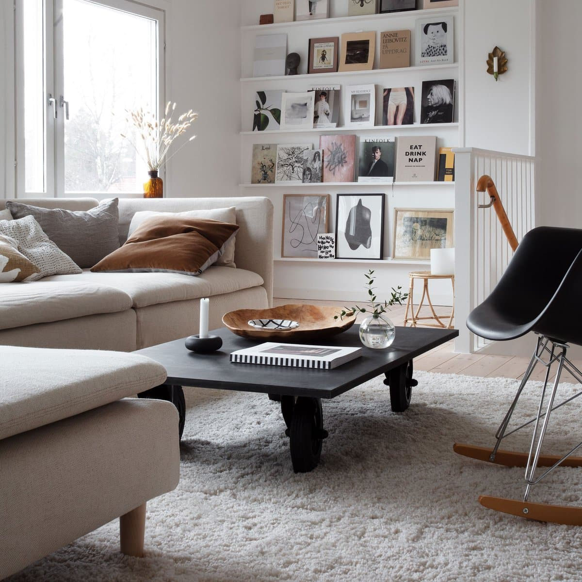 neutral living room with books on picture ledge and black coffee table