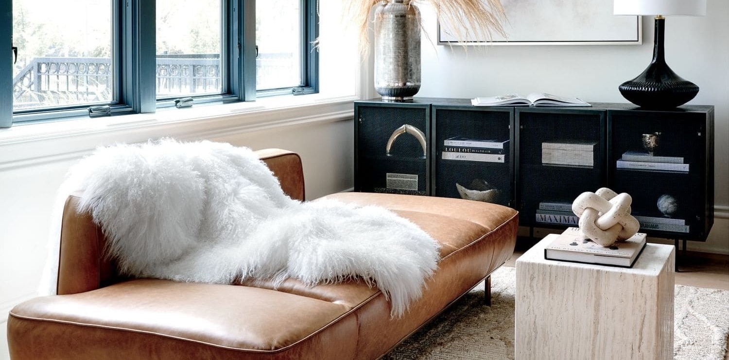 tan leather sofa with mongolian throw rug in loft apartment