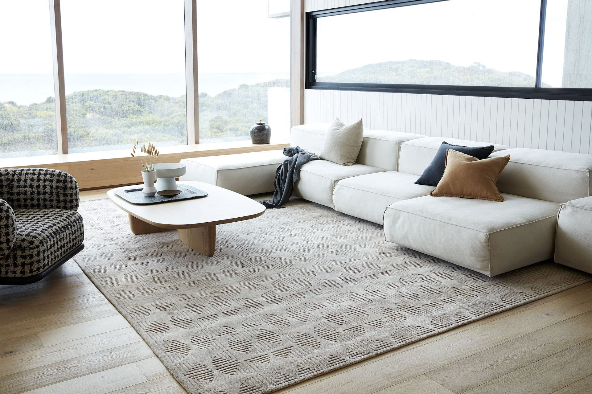 tribe home neutral living room with subtle patterned rug and large block sofa
