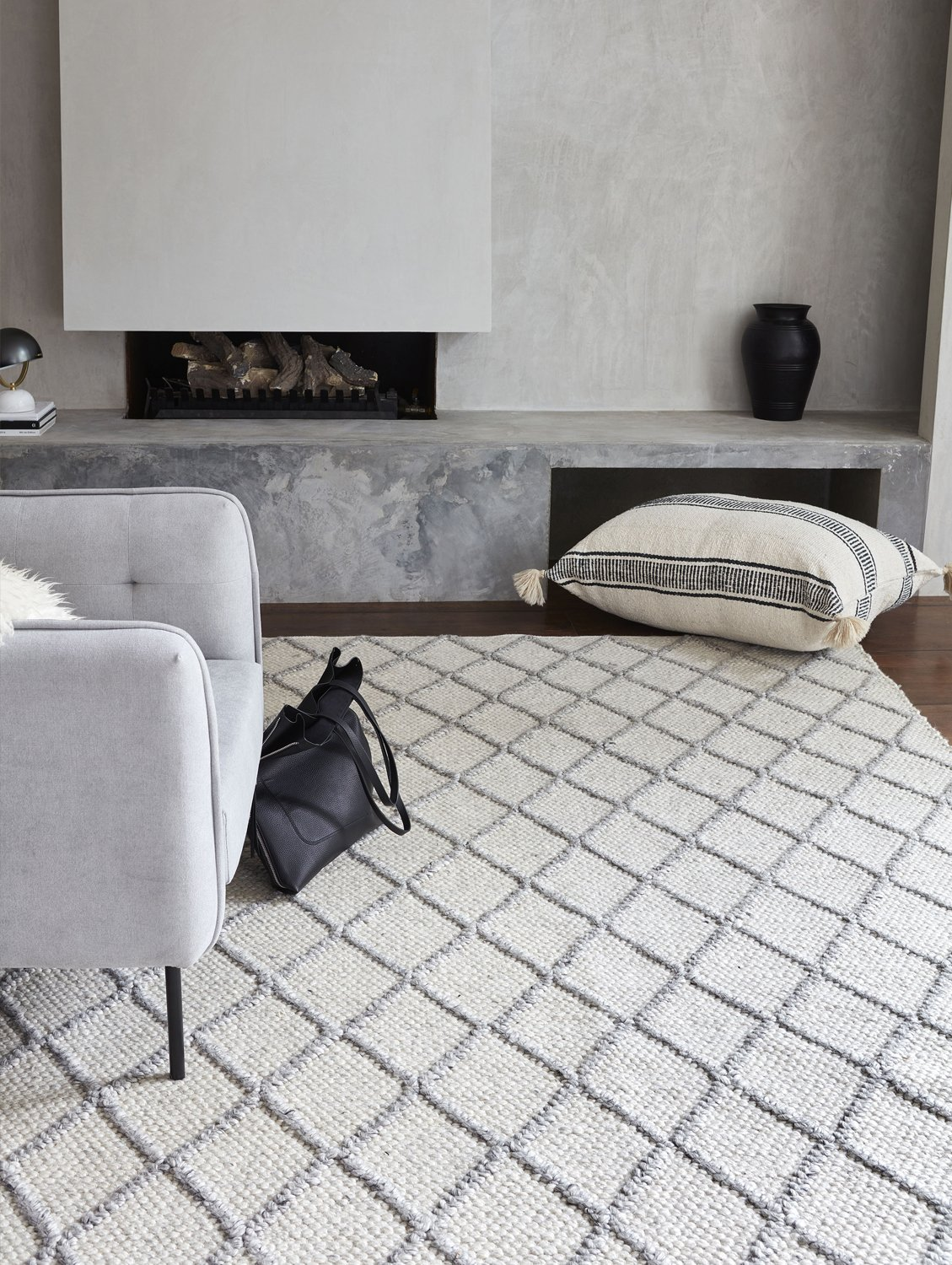 tribe home white and grey diamond rug in neutral living room with concrete effect wall