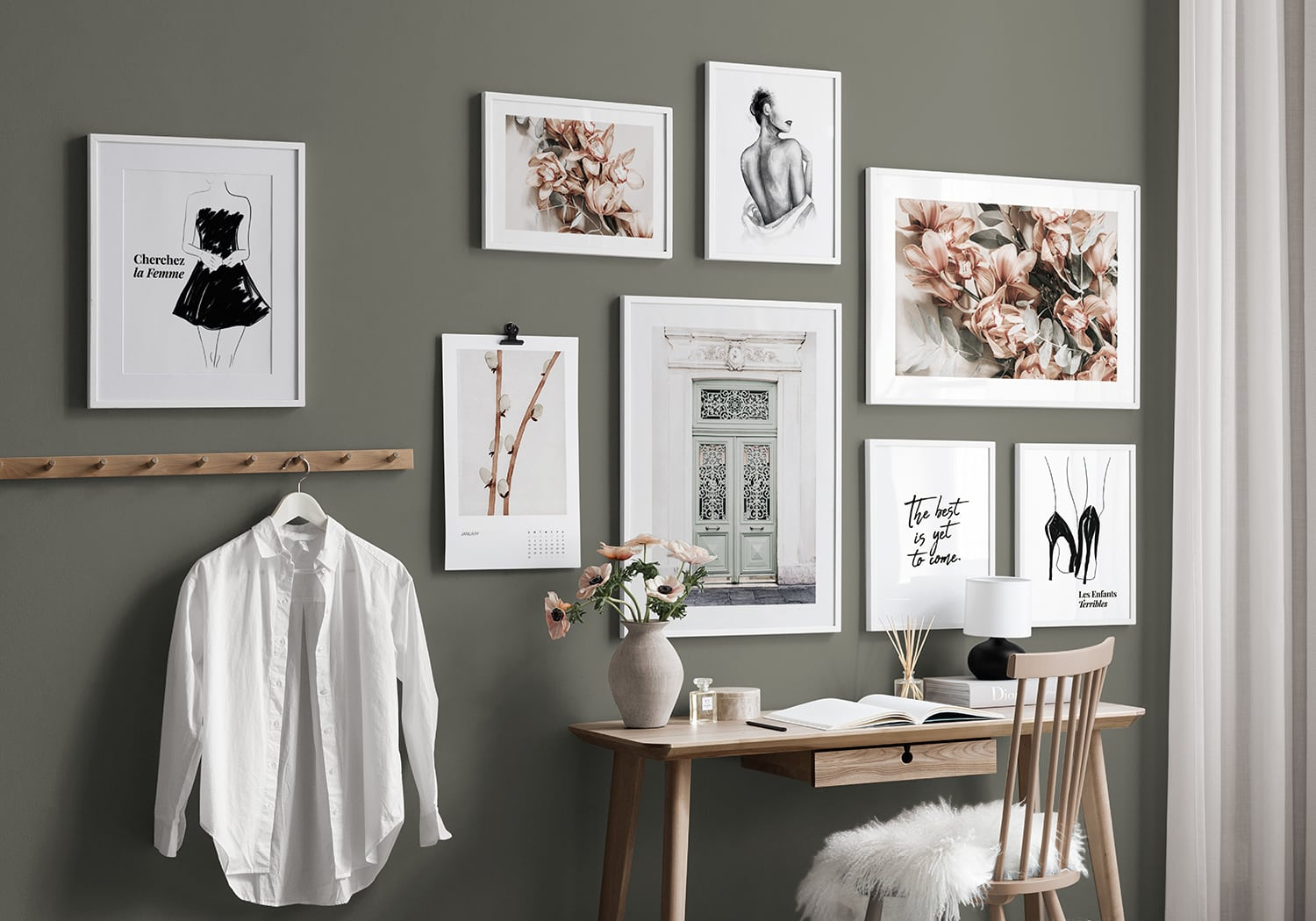 creating a gallery wall of art in white frames on olive green wall