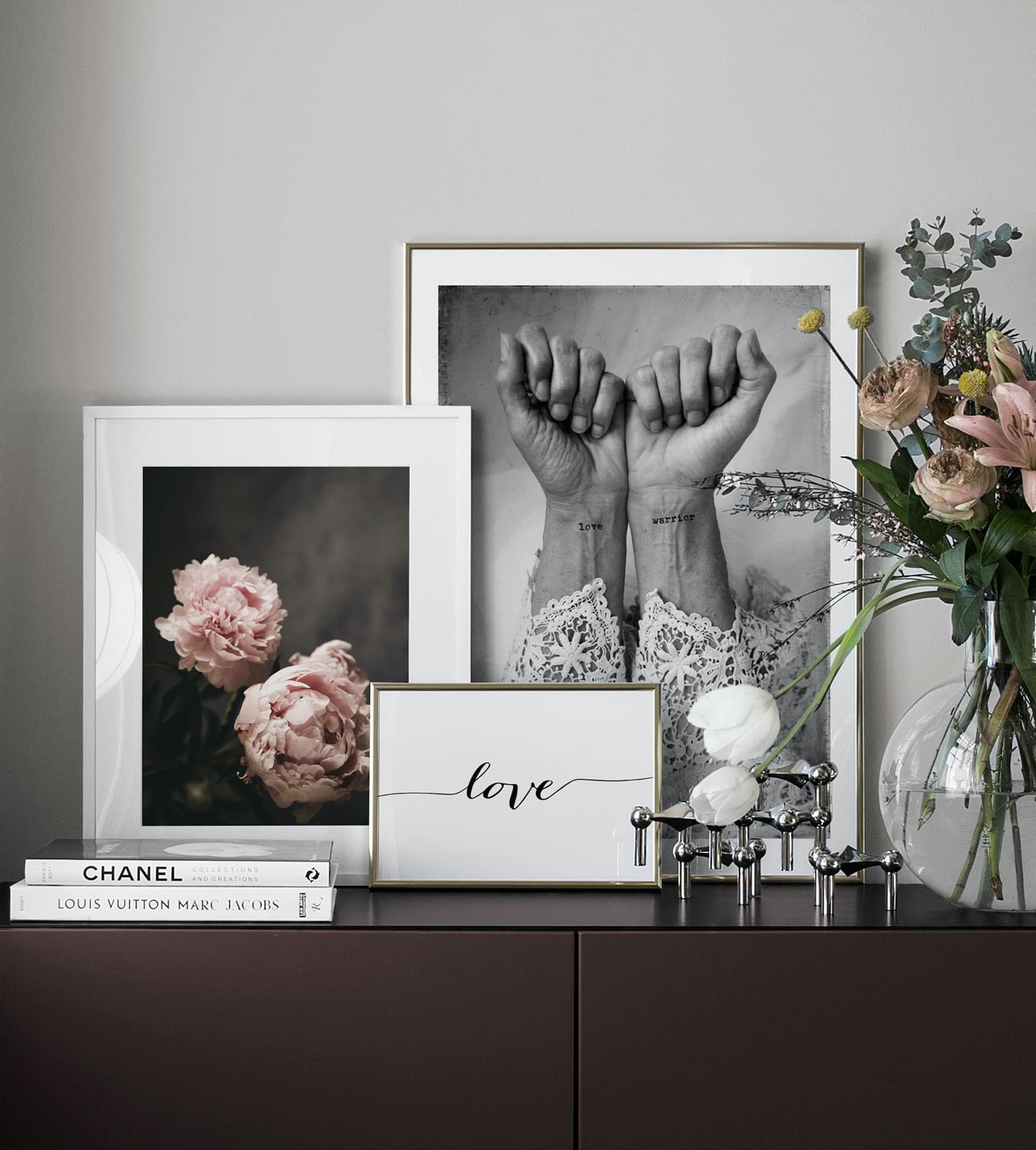 desenio art in thin gold frames leaning on dark brown sideboard