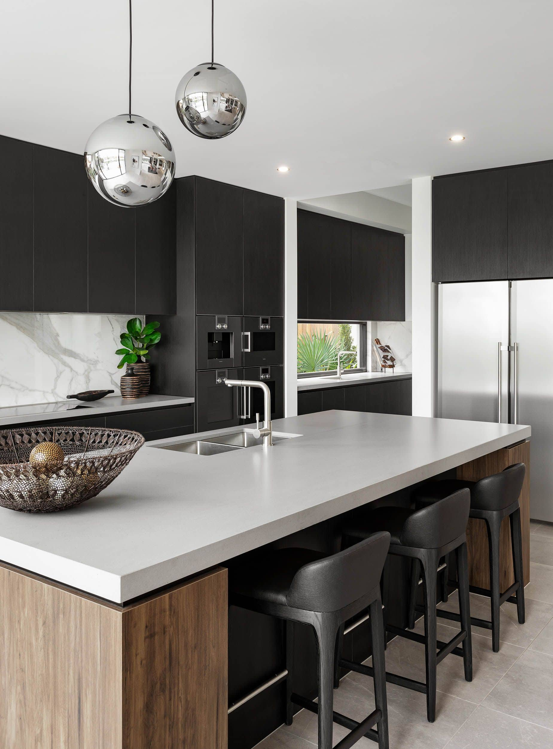 metricon black industrial kitchen with thick island bechtop and black cabinets